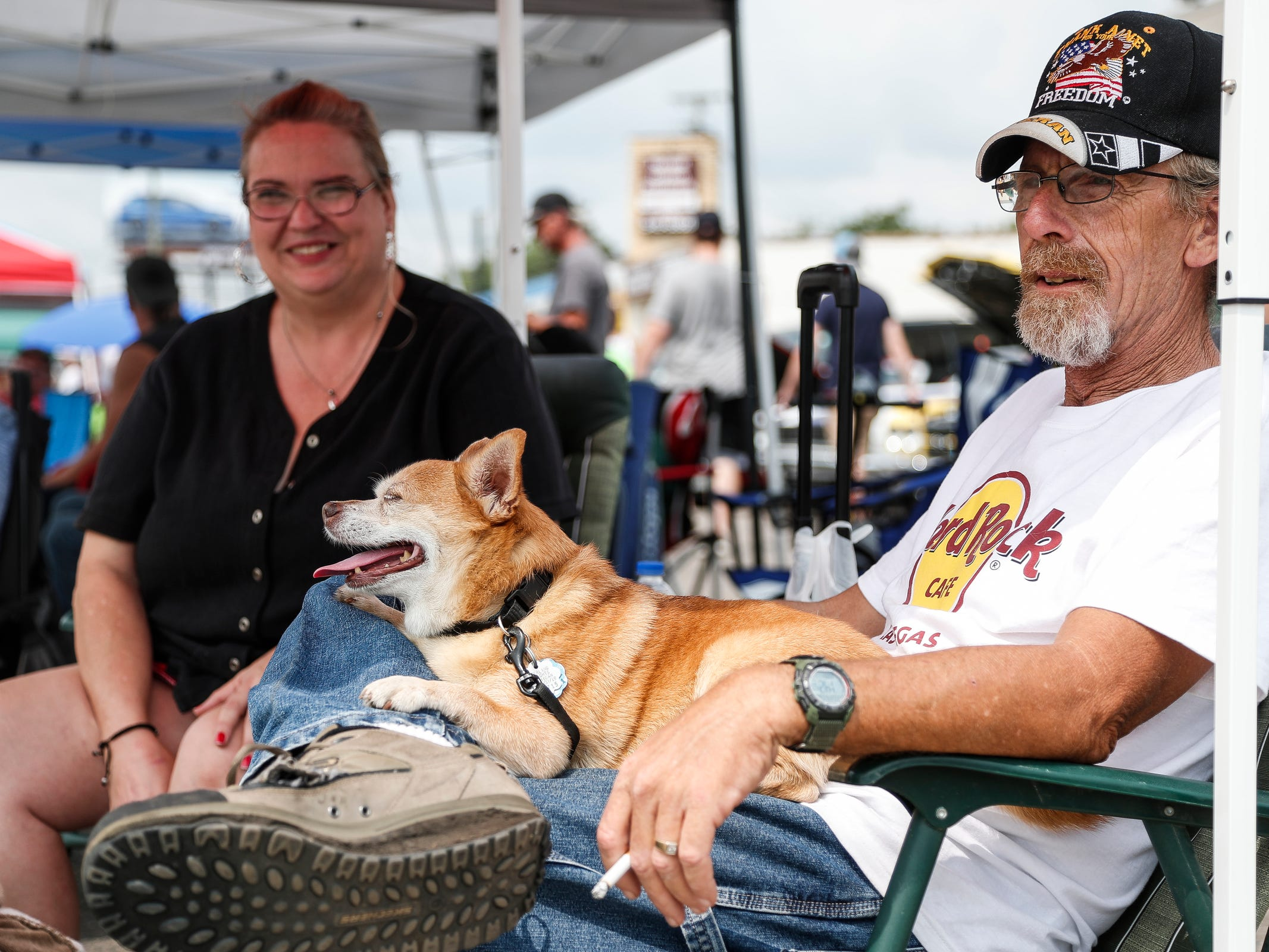 Norm Edgar of Sterling Heights, with his dog Chico, and girlfriend Mellissa Bonar of Bainbridge, Ohio, watch classic cars cruising along Woodward Avenue in Royal Oak during Woodward Dream Cruise, Saturday, August 18, 2018.