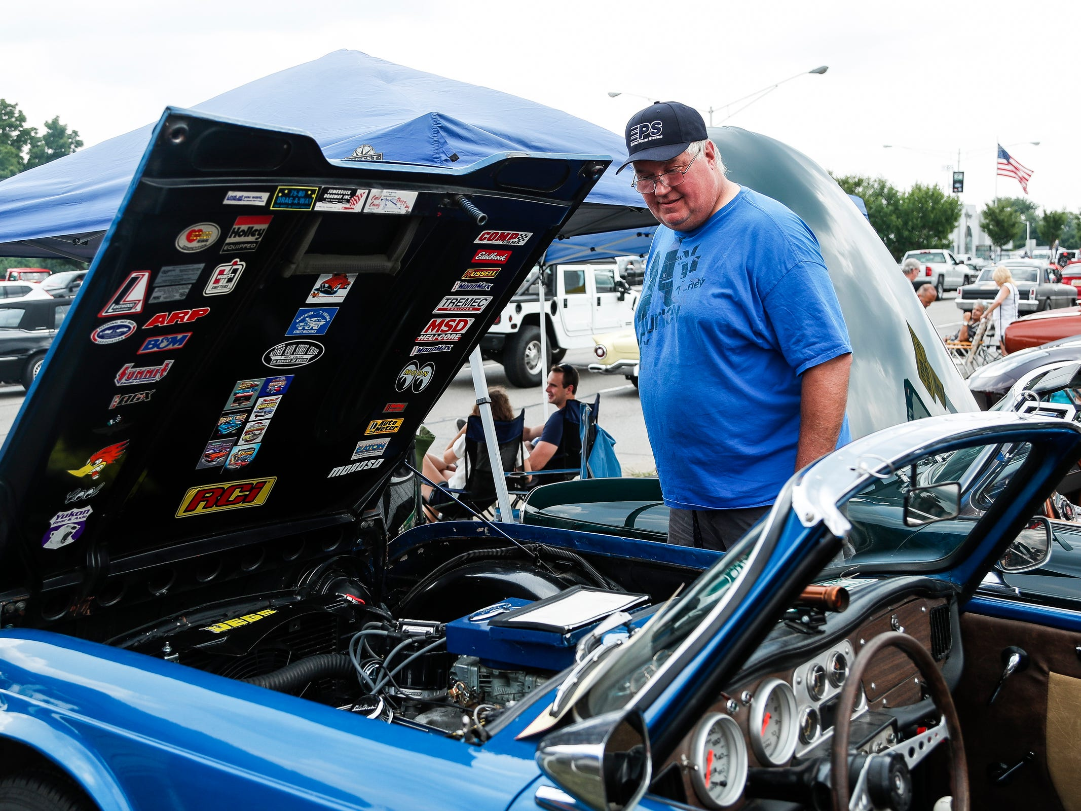 Gary Hudson of Harrison looks at the engine bay of a 1962 Triumph TR-4 along Woodward Avenue in Royal Oak during the Woodward Dream Cruise, Saturday, August 18, 2018.