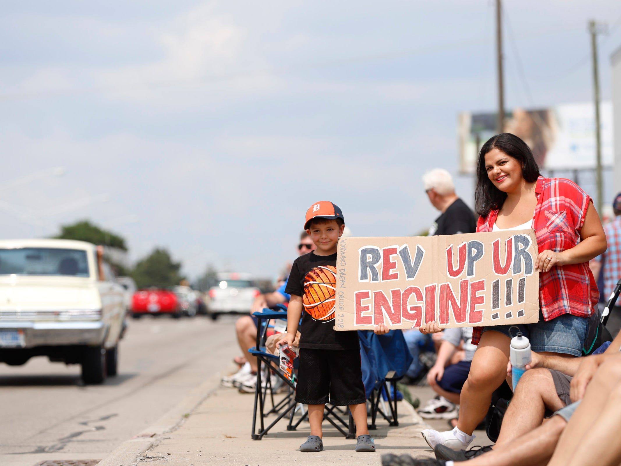 Rosario Marino, 5, and his mother Linda Marino, both of Royal Oak, hold a sign as they watch classic car cruising down Woodward Avenue near 13 Mile during the Woodward Dream Cruise, Saturday, Aug. 18, 2018.