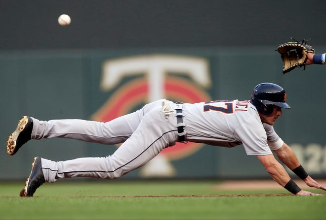 Detroit Tigers' Jim Adduci dives safely back to first against Minnesota Twins' first baseman Ehire Adrianza on a pickoff-attempt in the first inning of a baseball game Friday, Aug. 17, 2018, in Minneapolis.