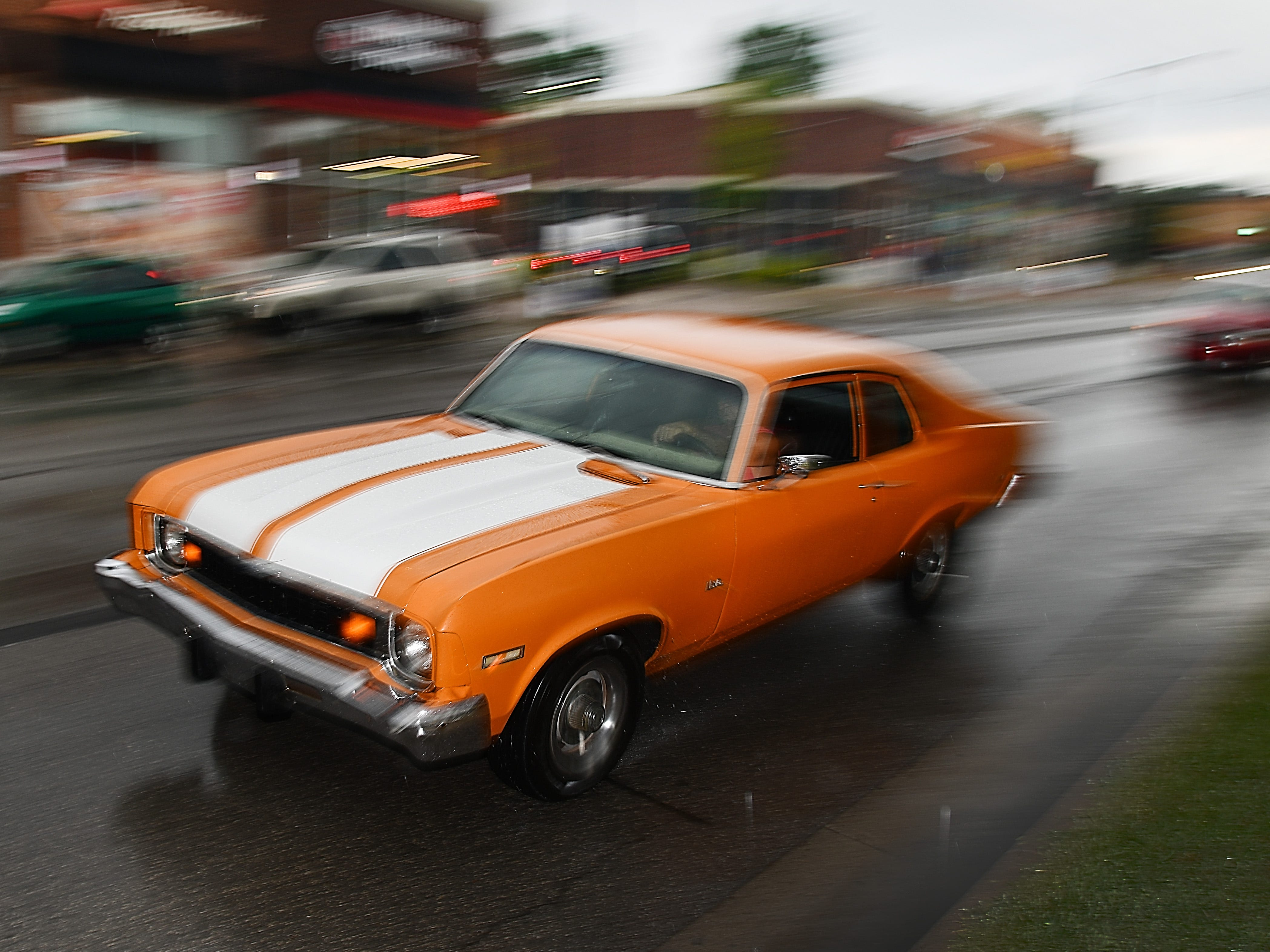 Cars make their way down Woodward Avenue in Ferndale as rain makes its way into the area during Dream Cruise 2018 on August 18, 2018.
