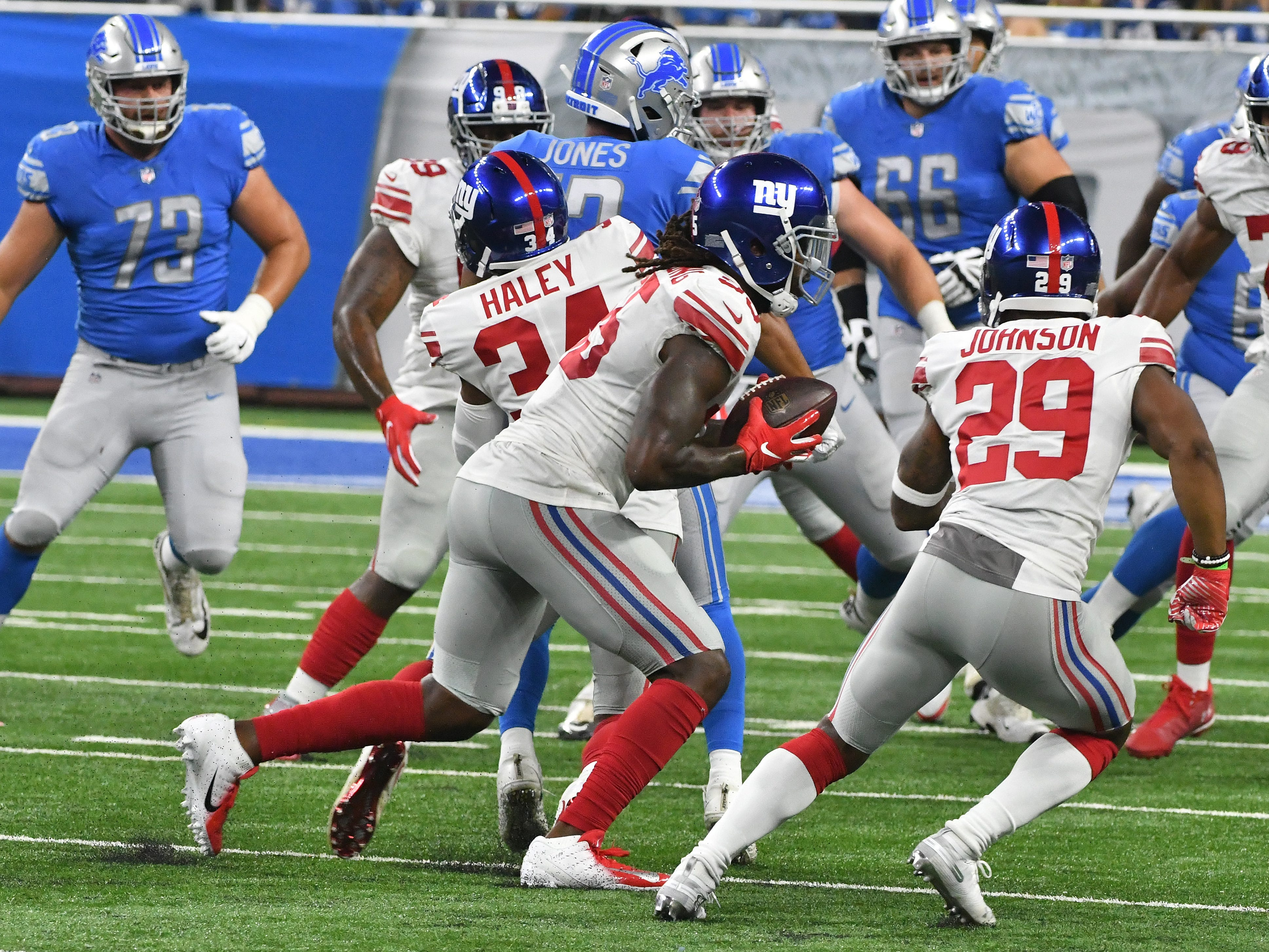 Giants' Ray-Ray Armstrong pulls in a ball that went through the hands of Lions T.J. Jones, bounced off his teammate Giants' Grant Haley and into his hands for an interception in the third quarter.