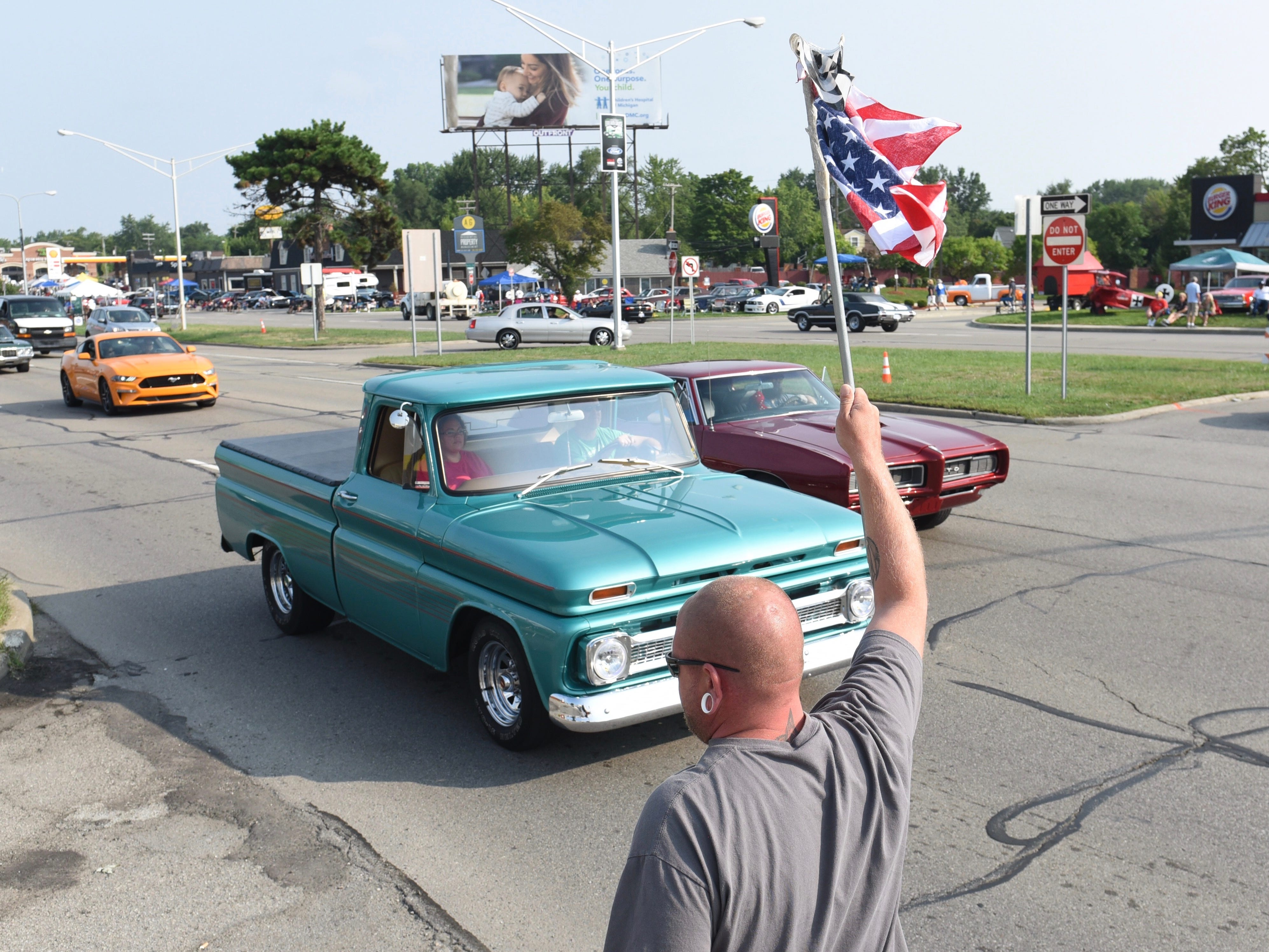 Josh Cavdill, of Dayton, Ohio, waves the American flag along Woodward Avenue in Royal Oak.