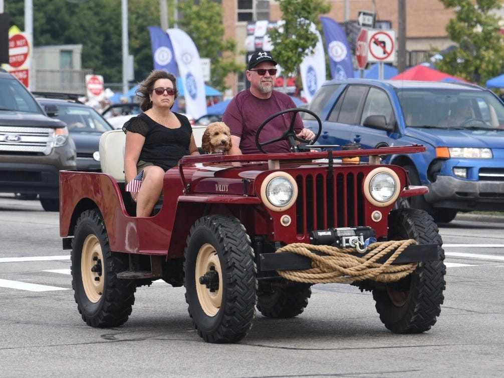 A classic Willys Jeep in a beautiful red and tan colors takes its turn cruising southbound on Woodward Avenue in Royal Oak.