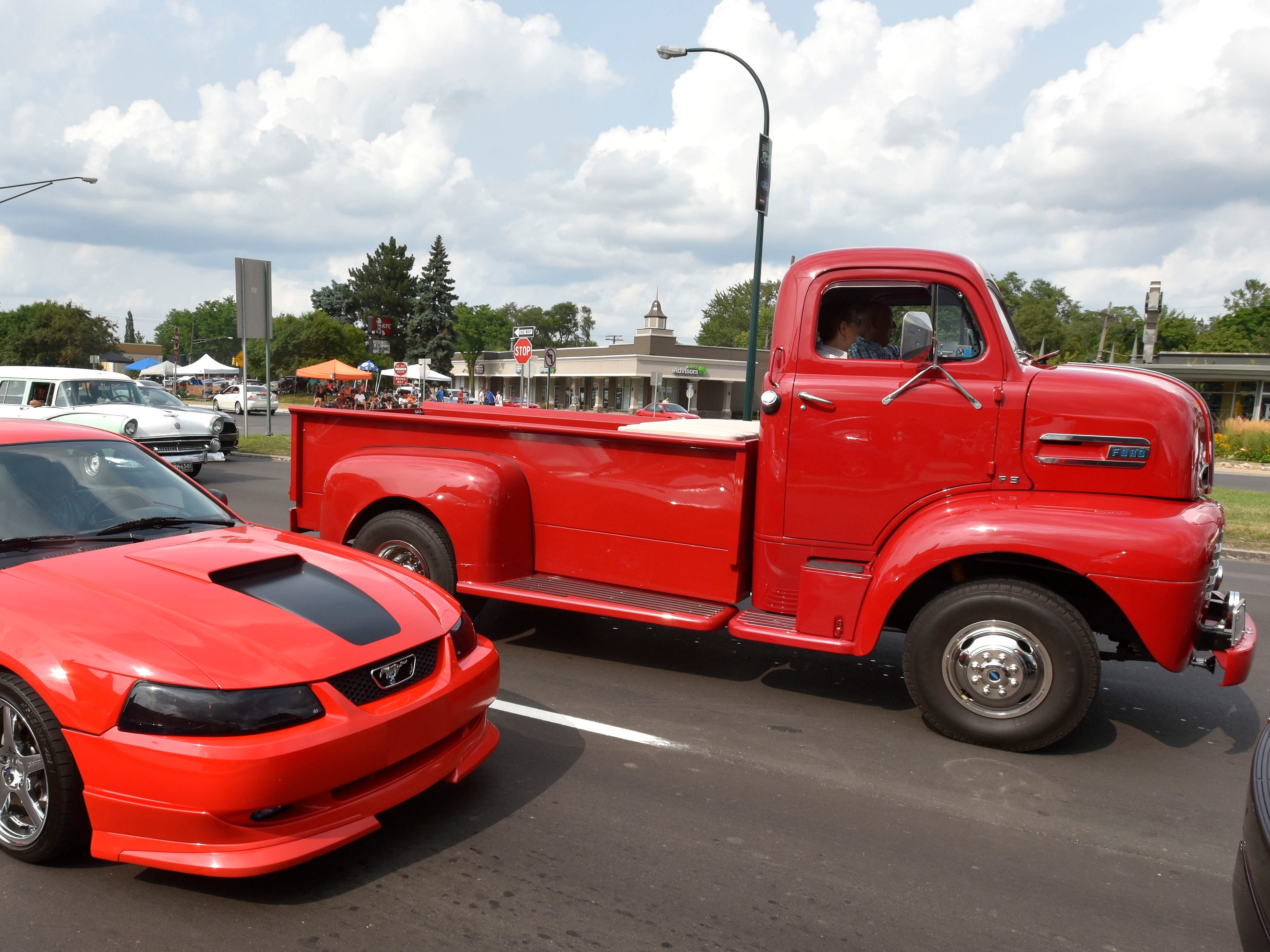 A Ford Mustang waits in traffic next to a customised 1940 Ford F3.