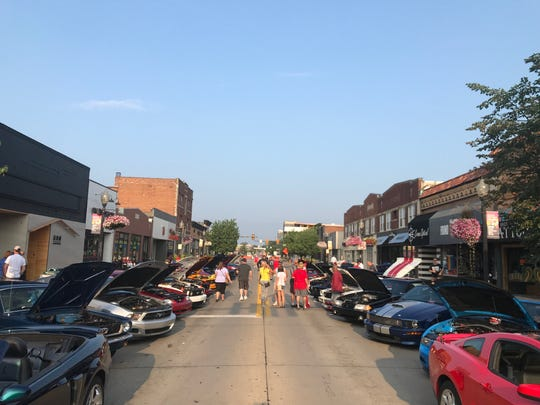 Volunteers work along Nine Mile east of Woodward to arrange roughly 1,000 Mustangs as the pony car owners arrived in the 8 o'clock hour in Ferndale.