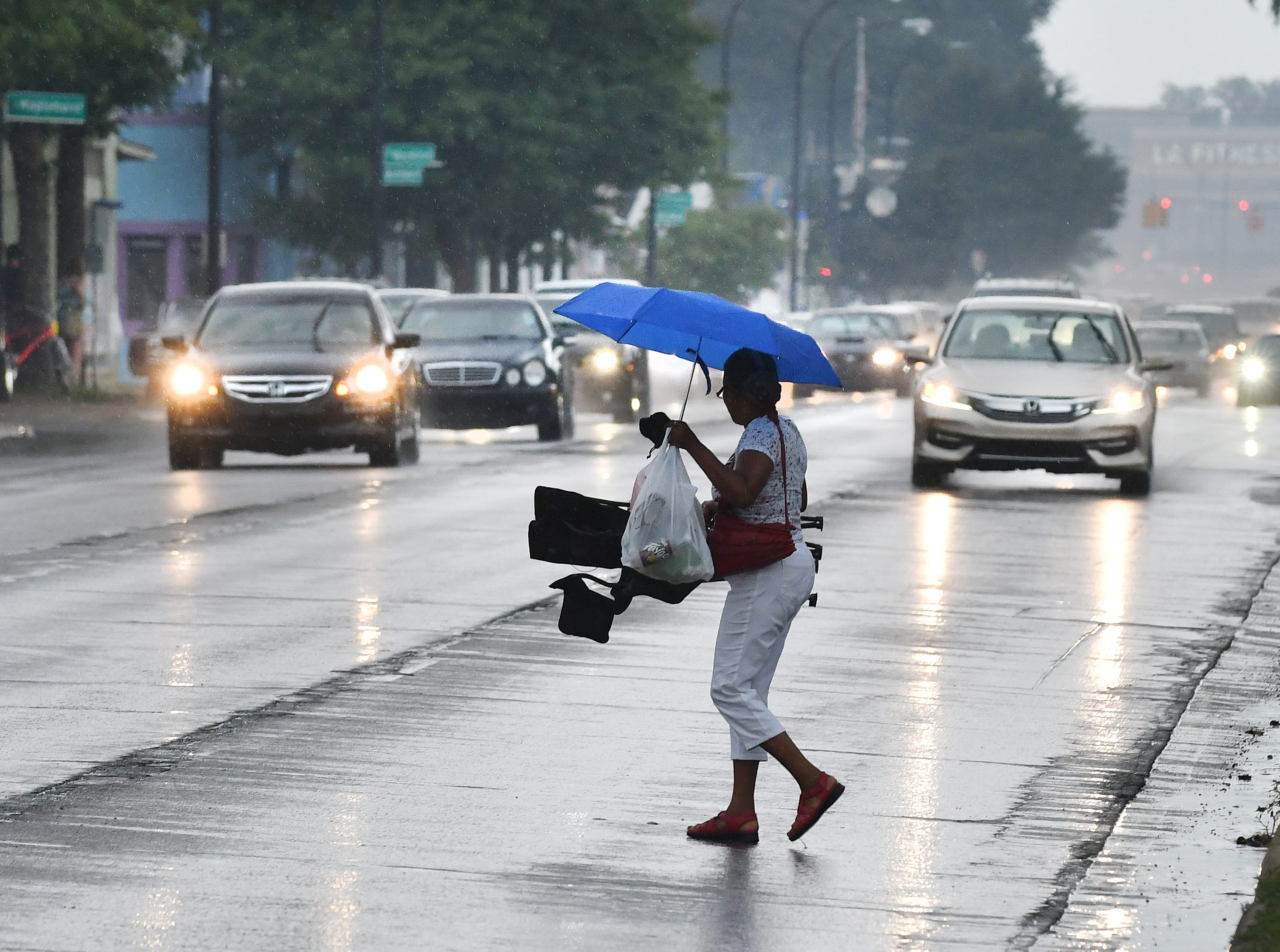 Car fans make their way off the median of Woodward Avenue as the rain starts fall Saturday evening in Ferndale.