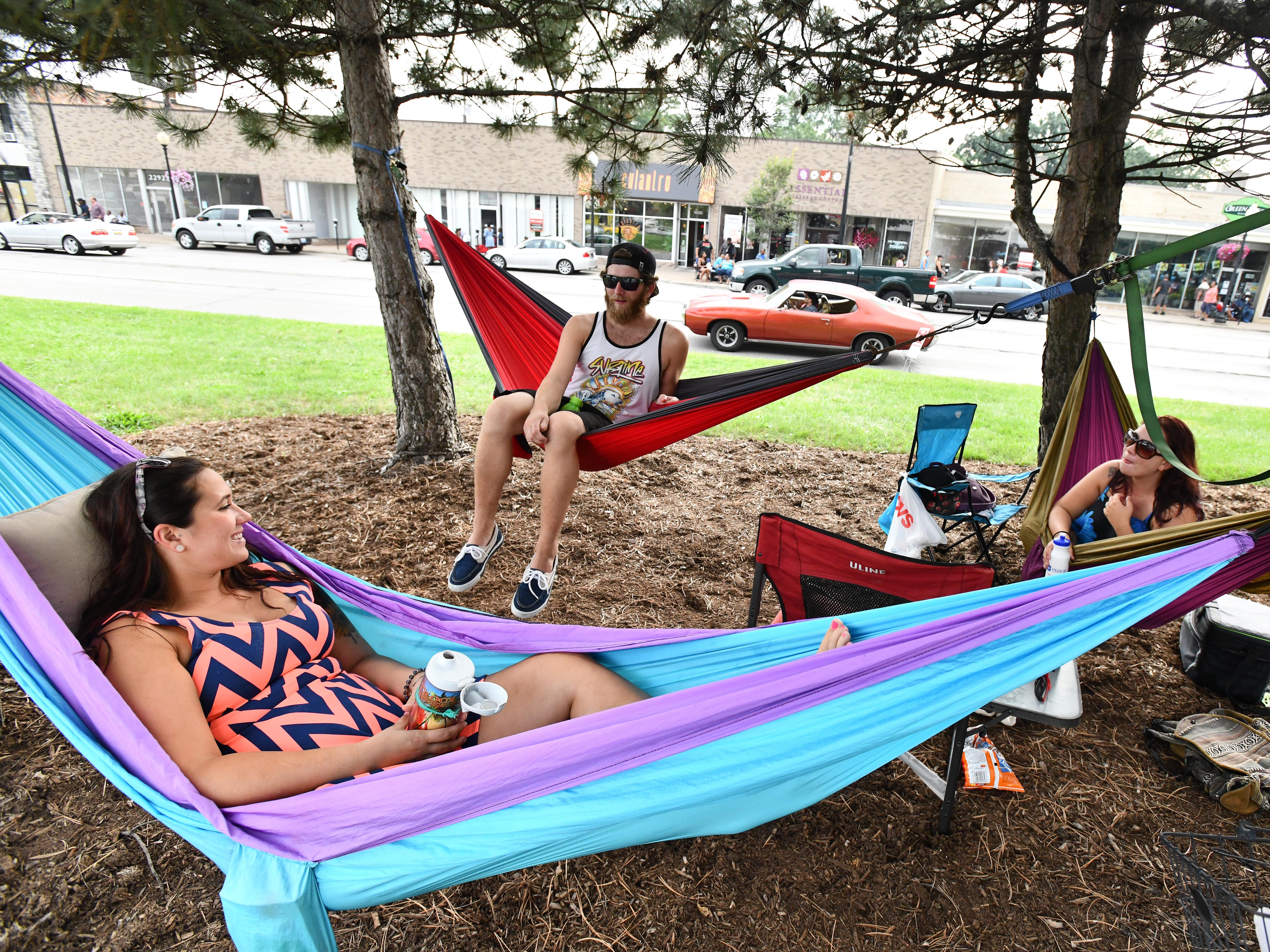 Ashley Rathka, Corey Walsh and Austen Walsh find the best spot for Dream Cruise watching on Woodward, hanging hammocks from trees in the middle of the divided highway in Ferndale.