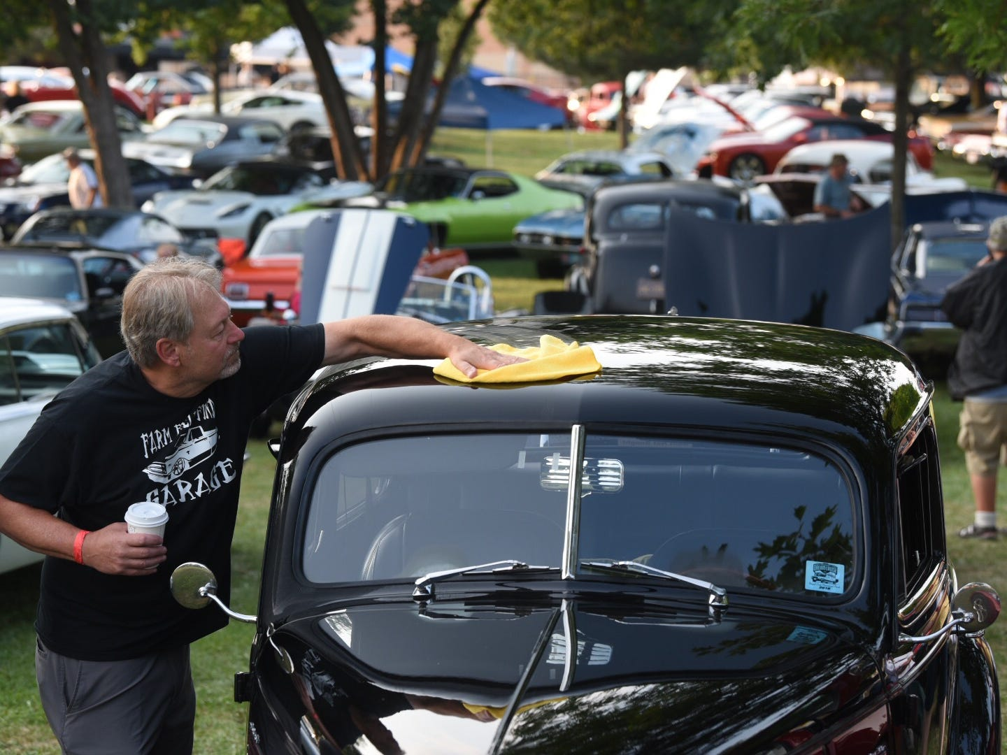 Gary Zacharias, of Hartland, Wisconsin, polishes a 1939 Chevy for the Woodward Dream Cruise.