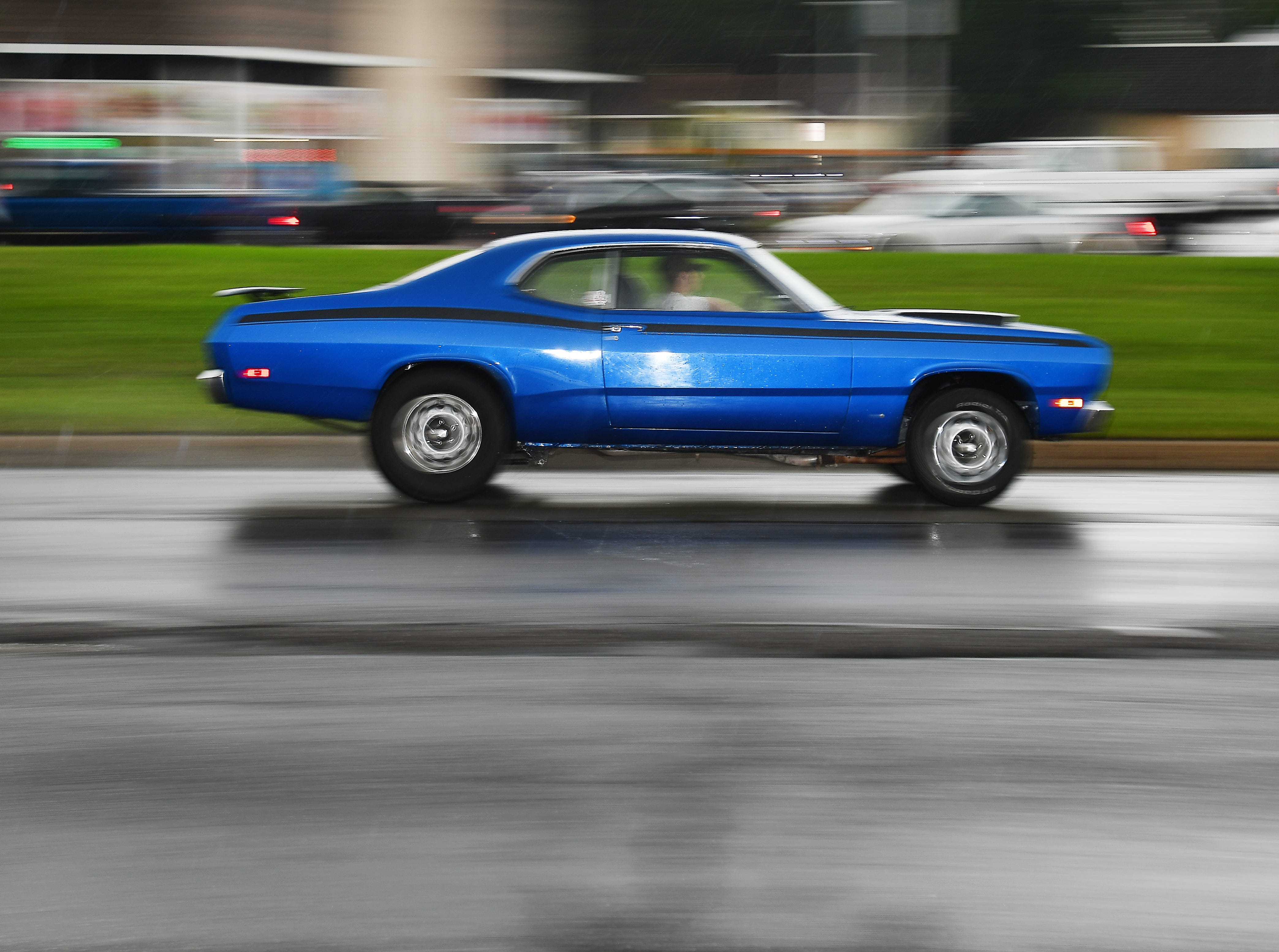 A muscle car cruises Woodward in the rain.
