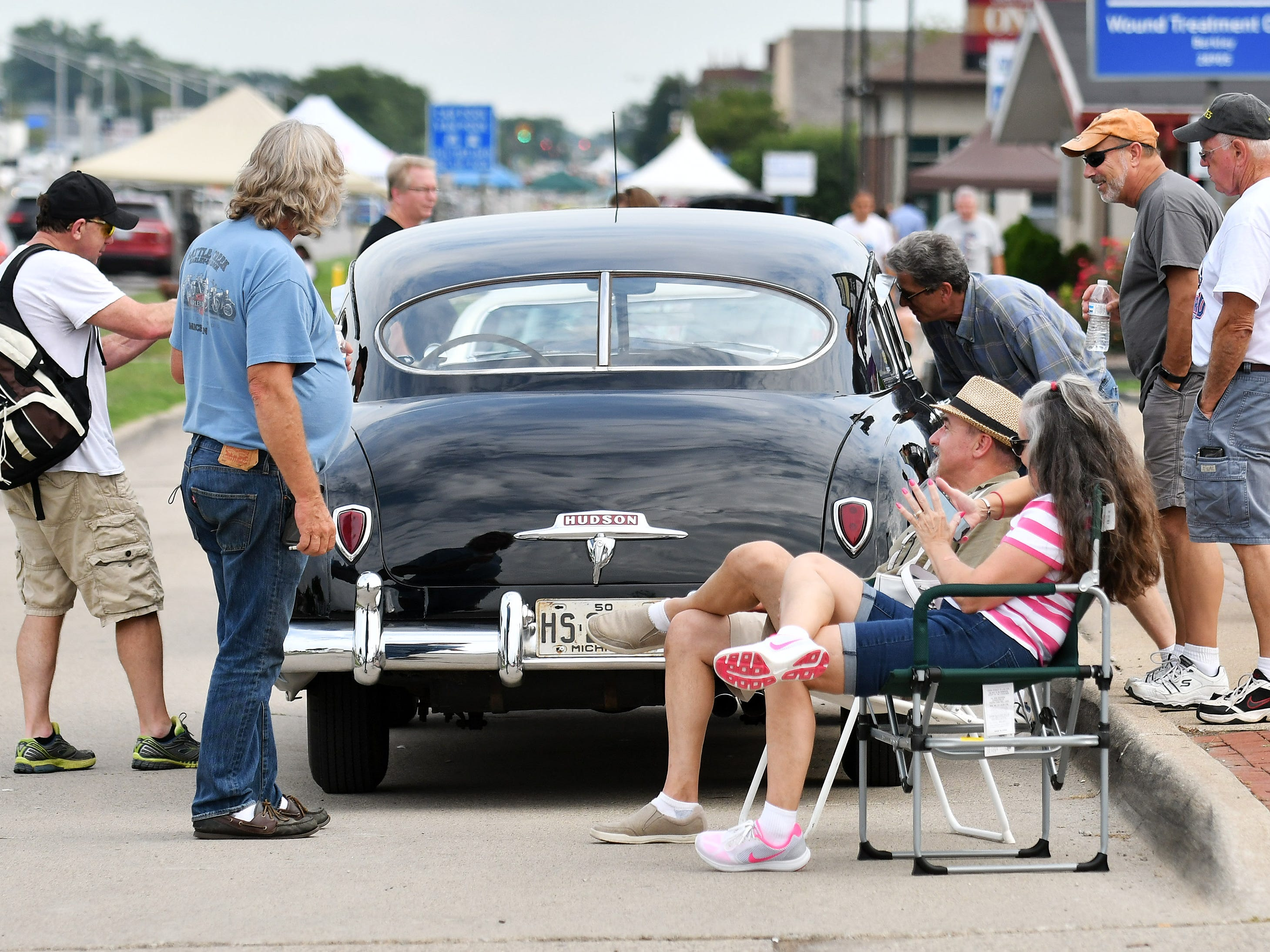 People check out the 1950 Hudson Super Six belonging to Heidi and Duane Sabella, seated at right, of New Baltimore parked along Woodward in Berkley, Mich. on Friday, Aug. 17, 2018.