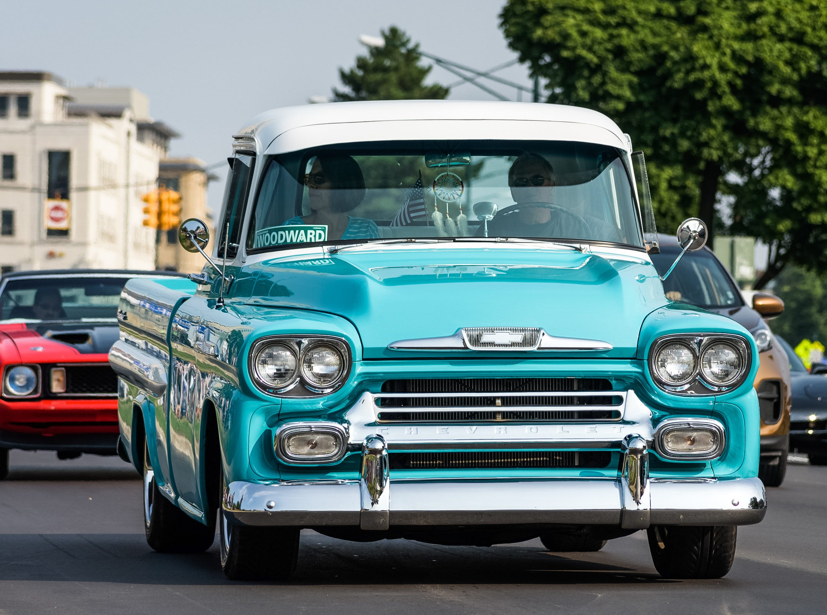 A vintage Chevrolet pickup drives up Woodward Avenue in front of the Chevrolet exhibit Saturday, August 18, 2018 during the Woodward Dream Cruise in Birmingham, Michigan.
