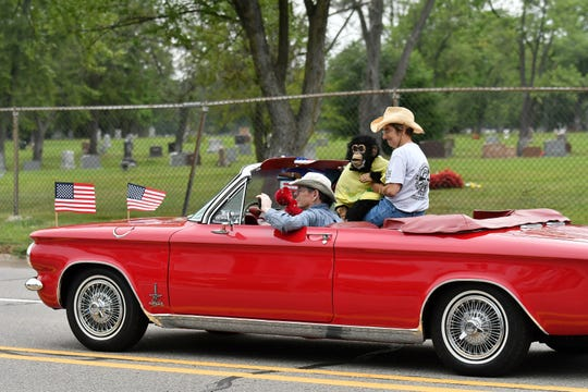 A couple with a monkey cruises in a Spyder in the Berkley CruiseFest Classic Car Parade.