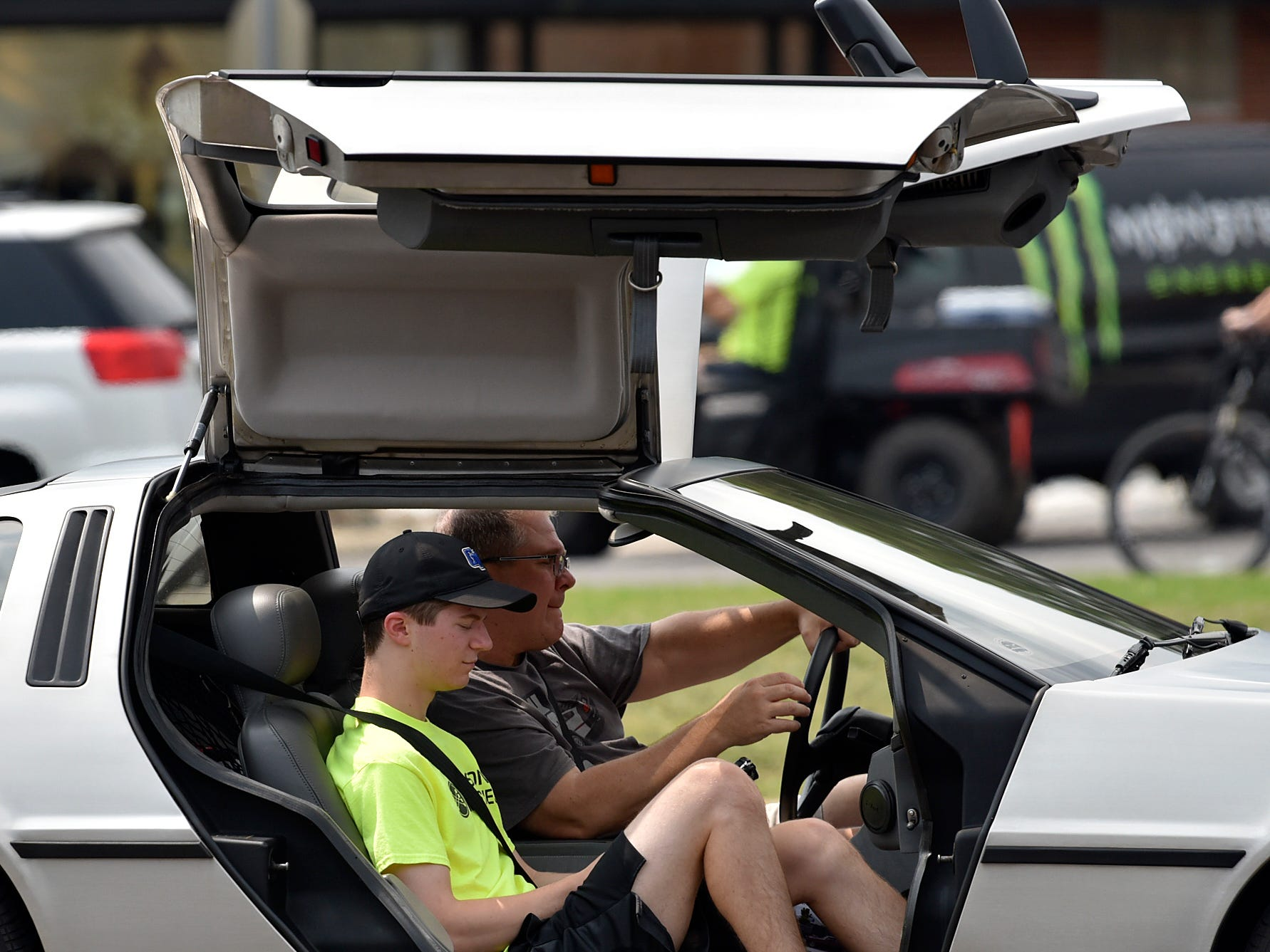 A pair of cruisers drive along Woodward Avenue with the gull doors of their Delorean open.