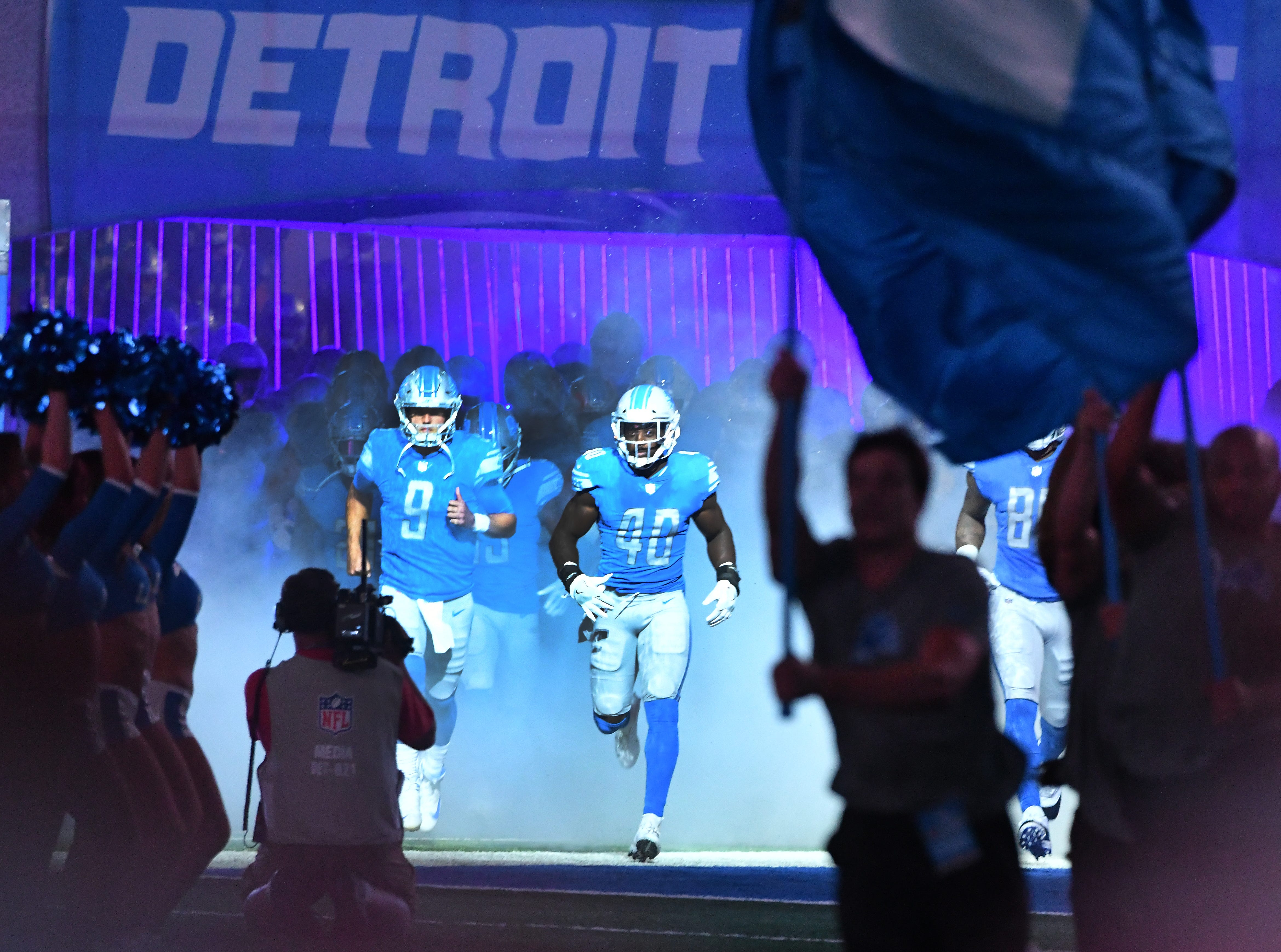 Quarterback Matthew Stafford and Jarrad Davis lead the Lions out of the tunnel for Detroit's first home preseason game against the New York Giants at Ford Field on August 17, 2018.
