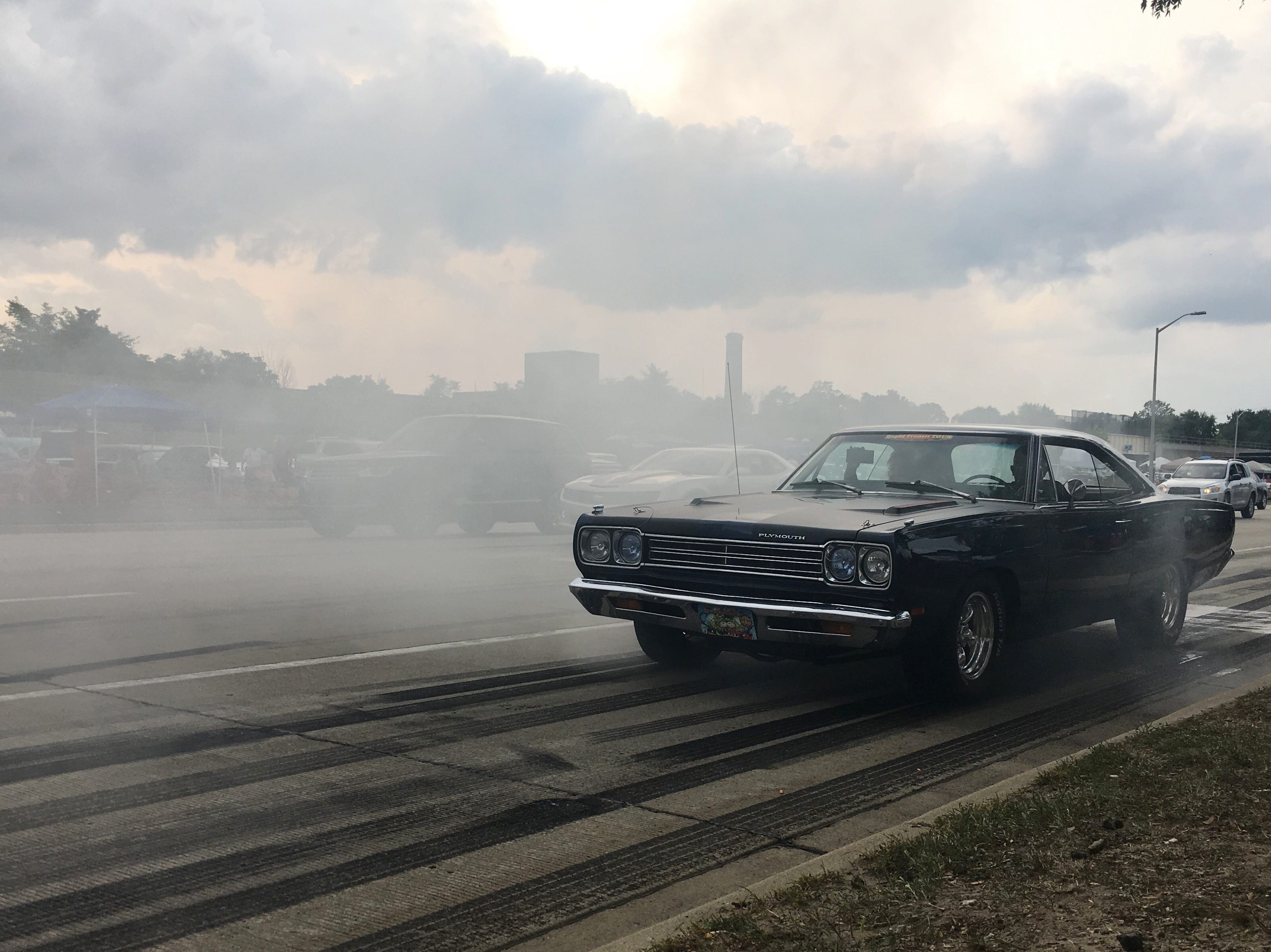 A Plymouth hot rod approaches through the smoke of another car's burnout on Woodward in Pontiac during the Woodward Dream Cruise in Pontiac, Michigan on Saturday, August 18, 2018.