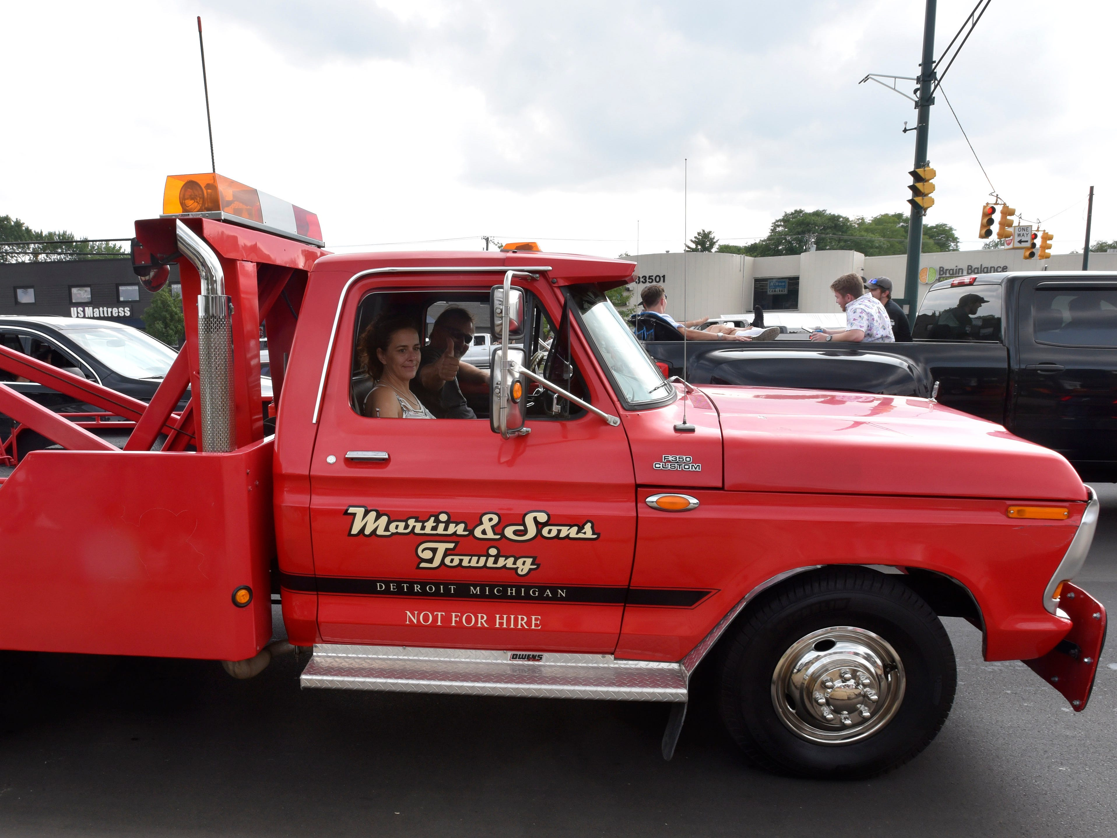 This couple rides in a 1978 Ford F 350 Custom tow truck (not for hire).