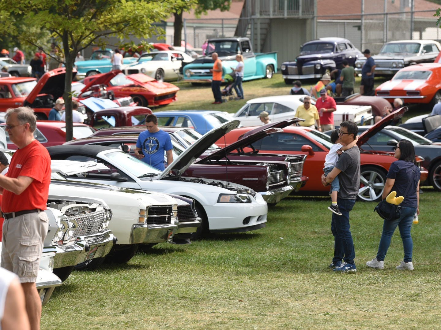 Families enjoy the weather at Memorial Park in Royal Oakand the large variety of vintage cars on display for the Woodward Dream Cruise.