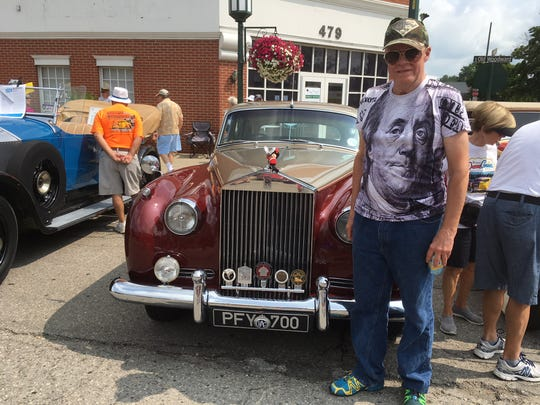 Peter Kohnken of Highland Township and his maroon and taupe 1957 Rolls Royce.