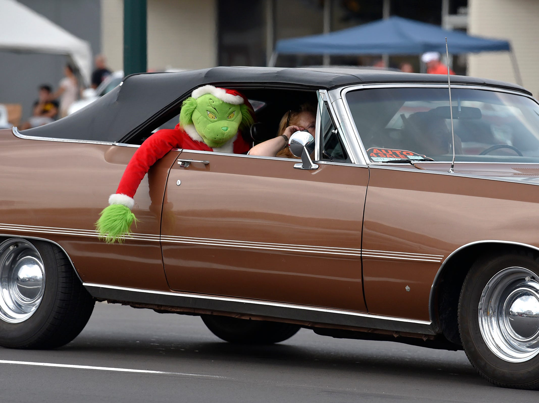A Grinch plush toy  rides in the back seat of a 1969 Chysler 300.