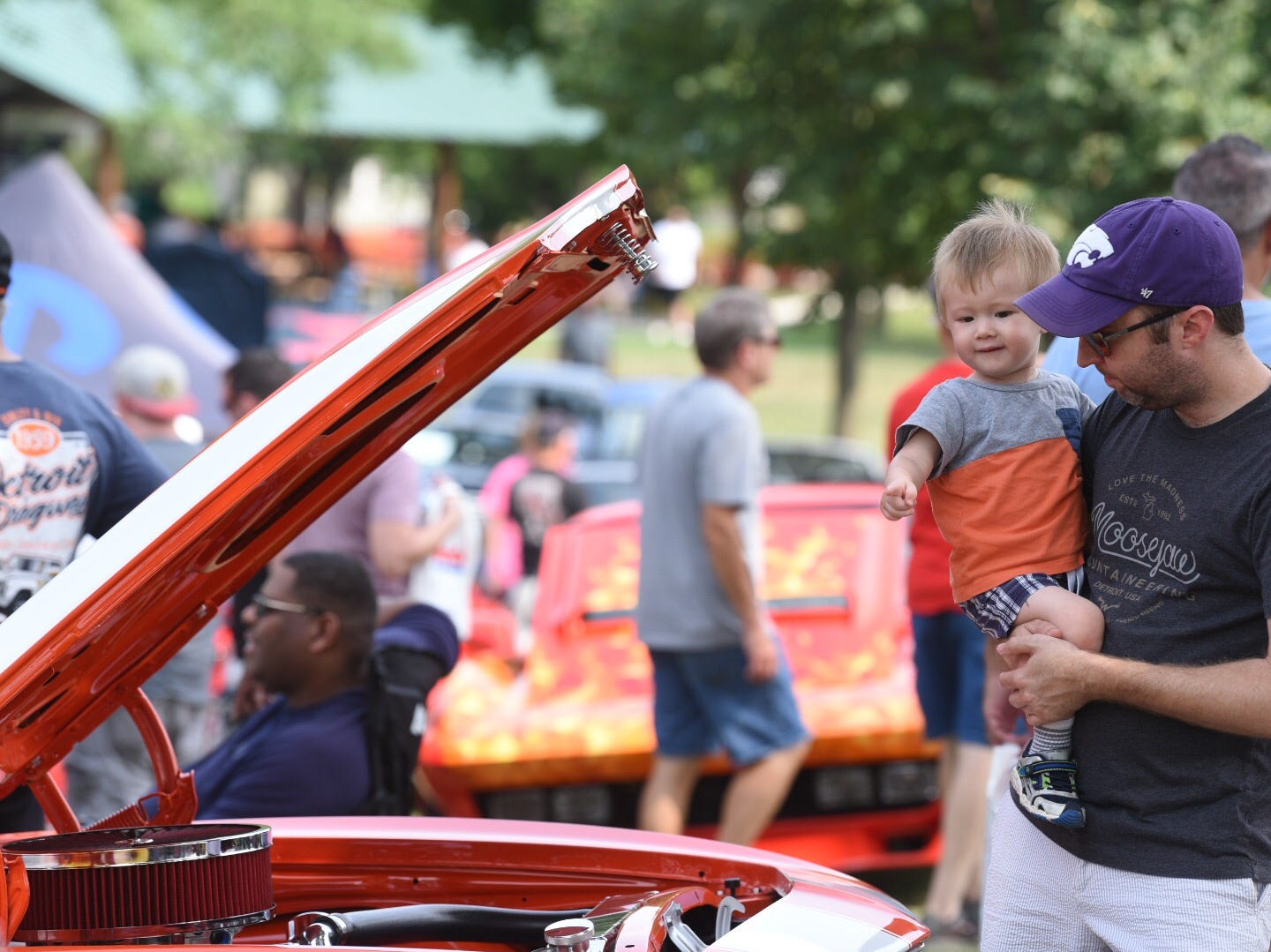 John Roberts of Bloomfield carries his son Evan as they look at tricked out cars at Memorial Park in Royal Oak for the Woodward Dream Cruise.