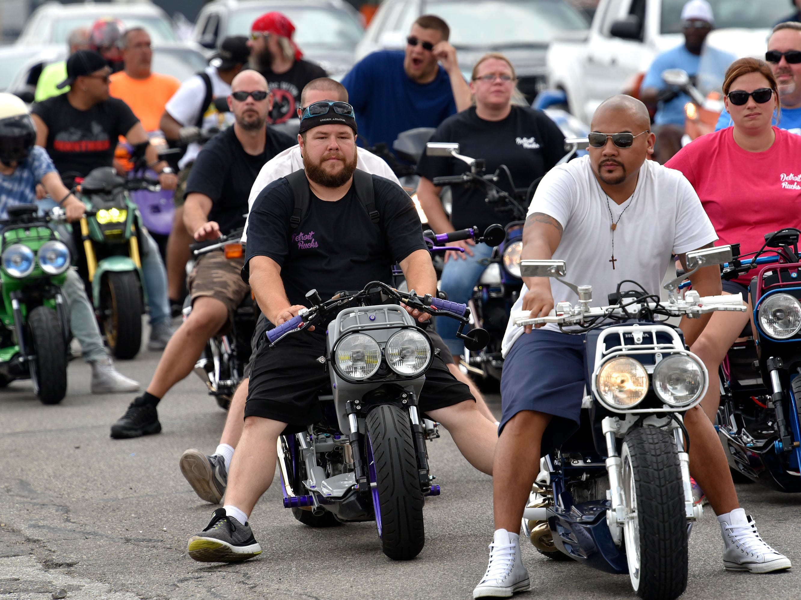Members of Detroit Rucks, a Facebook-based group of 50cc motor scooter owners, wait in traffic.