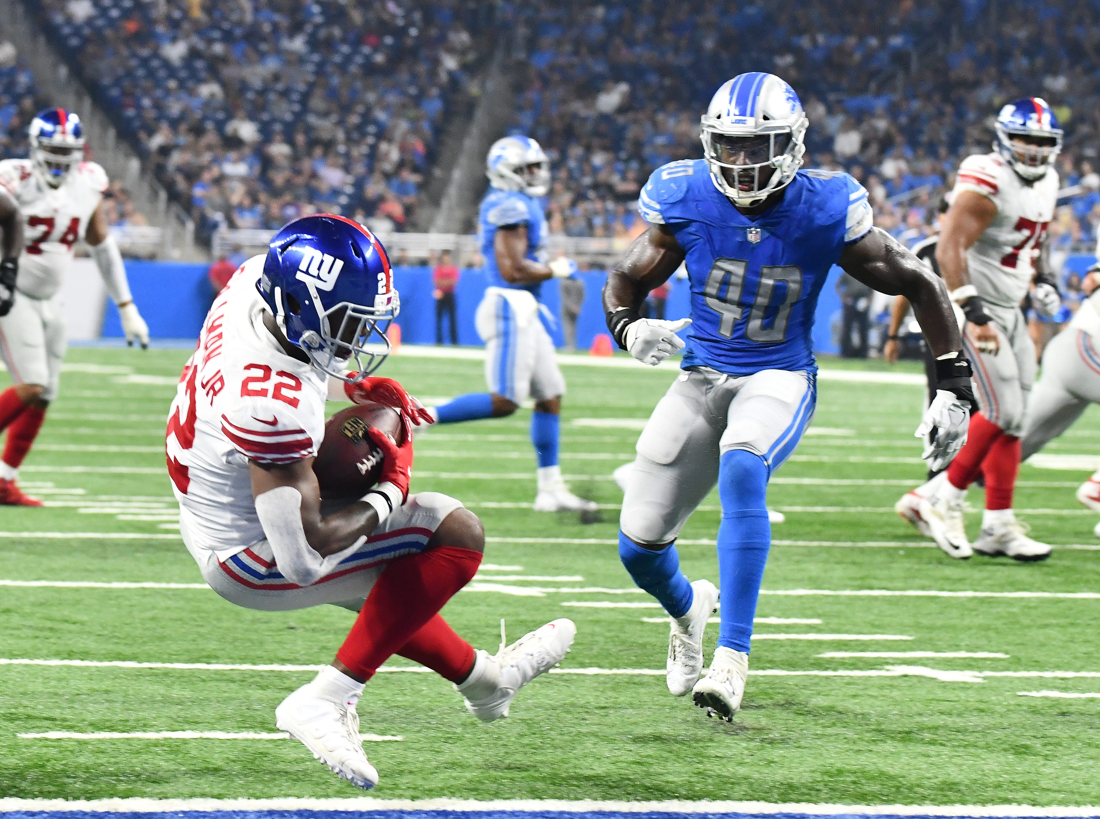 Giants' Wayne Gallman Jr. steps back into the end zone on a touchdown completion in front of Lions' Jarrad Davis in the second quarter.