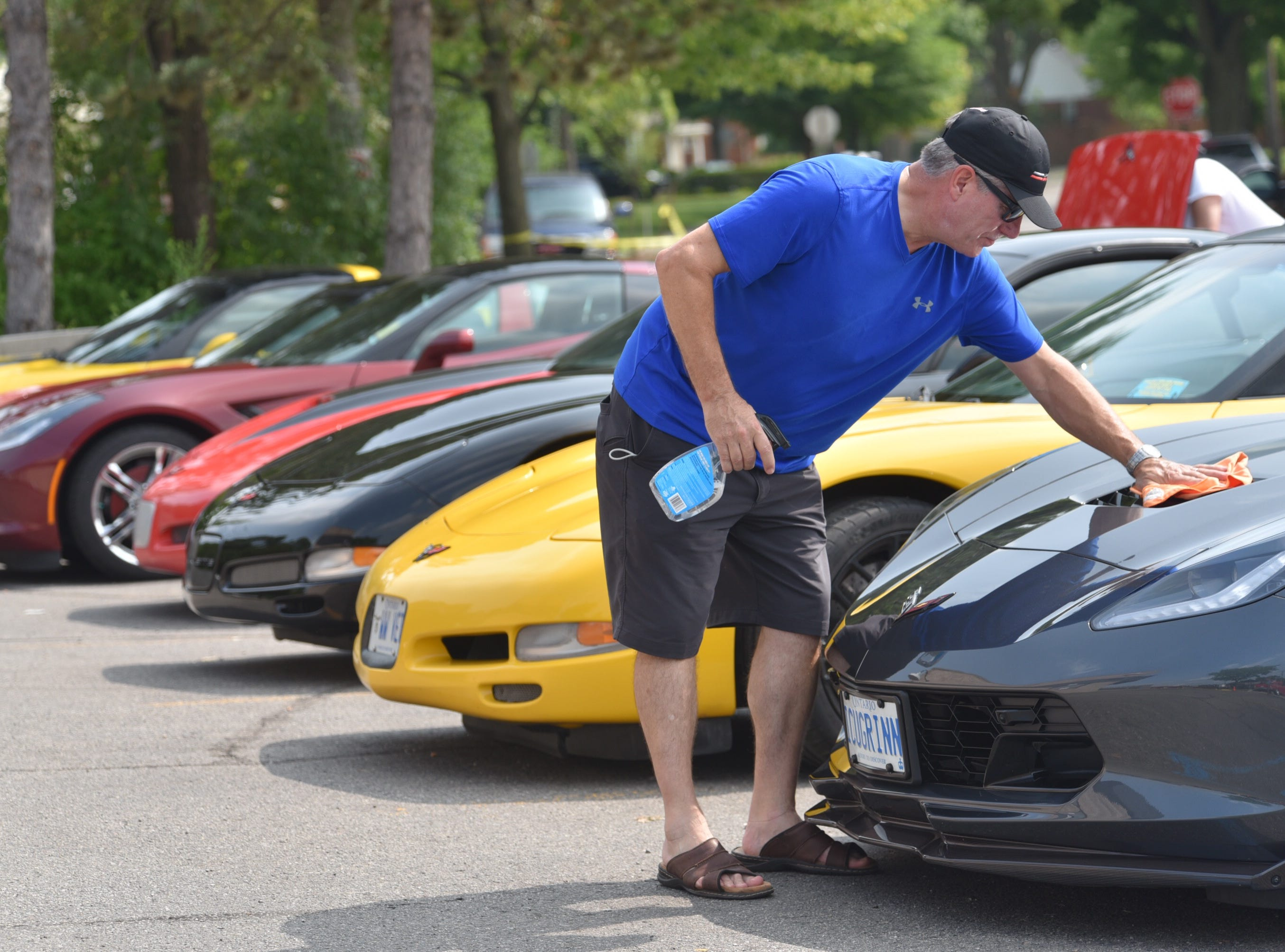 Richard Boyes, 66, of Ajax, Ontario, wipes down his 2017 Chevy Grand Sport Corvette in front of other Corvettes from a Corvette Internet forum group from Toronto.