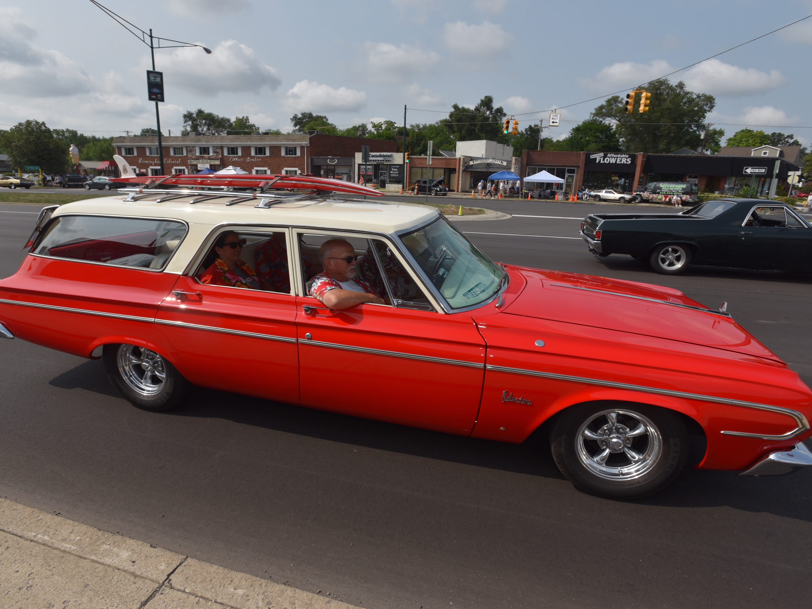 A surfboard is displayed on top of this 1964 Plymouth Belvedere wagon Saturday morning at the Woodward Dream Cruise.