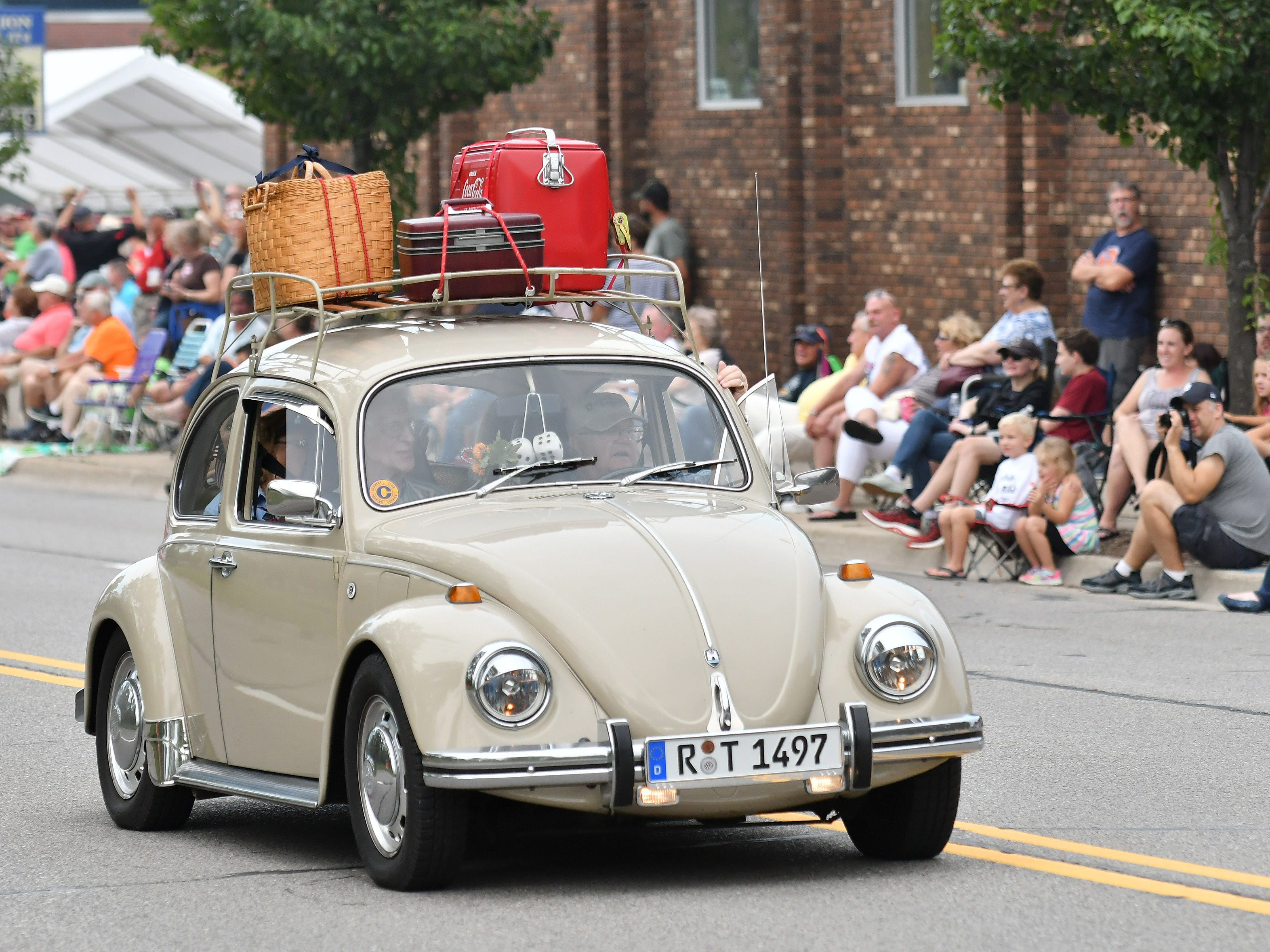 A Volkswagen Beetle rolls in the Berkley CruiseFest Classic Car Parade.