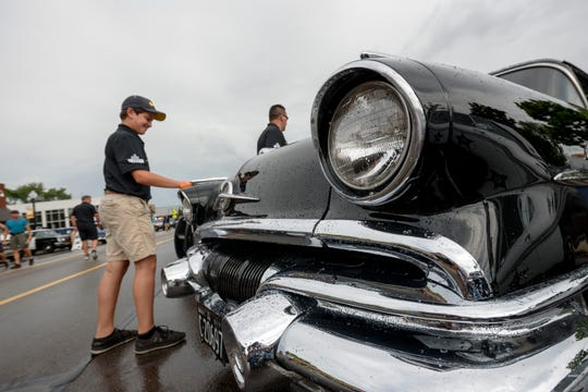 Adriano Tonin, 12, of LaSalle, Ontario, wipes the rain from a 1957 Pontiac Laurentian police vehicle that is owned by LaSalle's police department before the start of the 18th annual Ferndale Lights and Sirens Parade.
