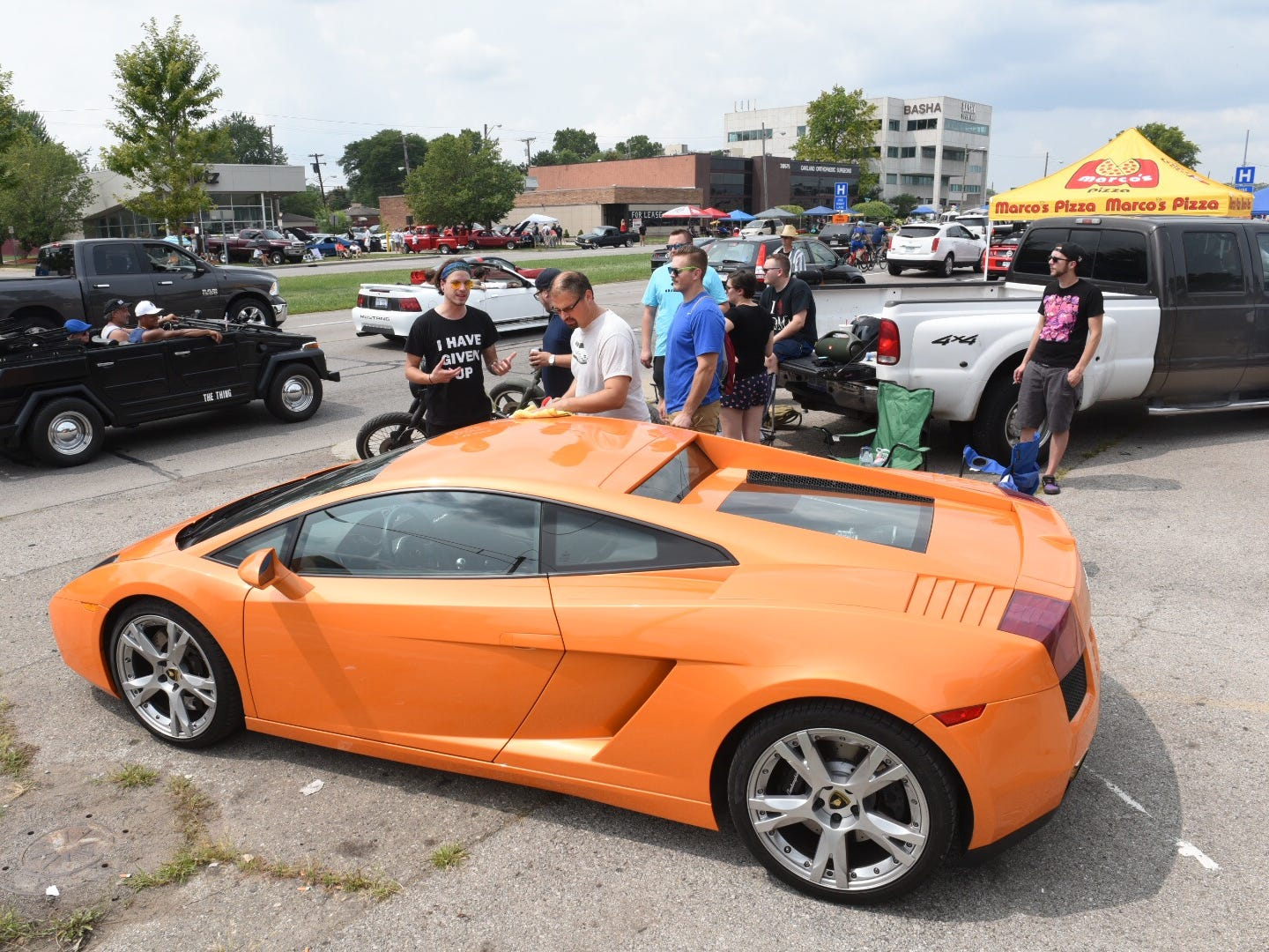 A Lamborghini Gallardo draws a crowd, while a VW Thing cruises by.