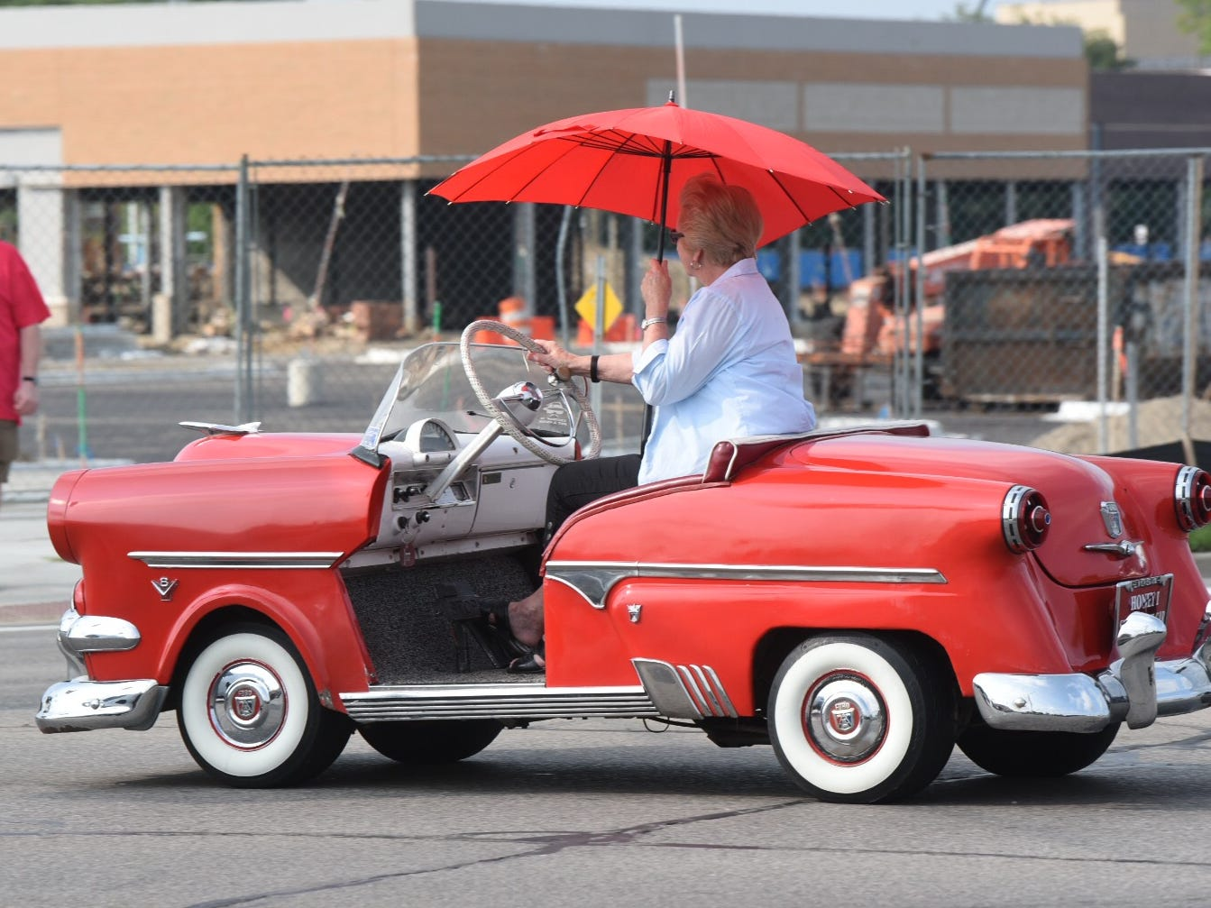 An umbrella shades this driver in her  mini convertible during the Woodward Dream Cruise in Royal Oak.