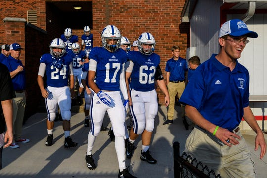 Aaron Coomer, right, leads the Memorial Tigers out of the locker room to prepare for their season opening match against the Jasper Wildcats at Enlow Field in Evansville, Ind., Friday, Aug. 17, 2018. The Tigers defeated the Wildcats 30-7.