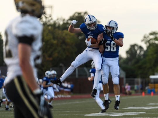 Memorial's Branson Combs (8) celebrates making the first touchdown of the game with his teammate Andrew Dehner (58) during the first quarter against the Jasper Wildcats at Enlow Field in Evansville, Ind., Friday, Aug. 17, 2018.