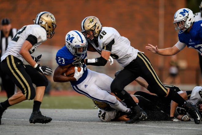 Memorial's Darius Johnson (23) is tackled by Jasper's Kyle Hedinger (48) and Isaac Bartley (24) during the second quarter at Enlow Field in Evansville, Ind., Friday, Aug. 17, 2018. The Tigers defeated the Wildcats 30-7 in the season opening game.