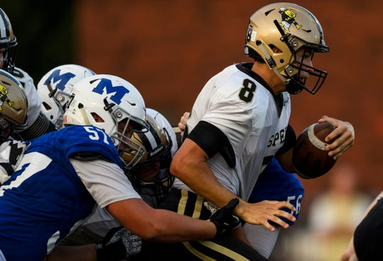Jasper's Jacob Ahlbrand (8) runs through a sea of Memorial Tiger defensemen during the second quarter at Enlow Field in Evansville, Ind., Friday, Aug. 17, 2018. The Tigers defeated the Wildcats 30-7 in the season opening game.