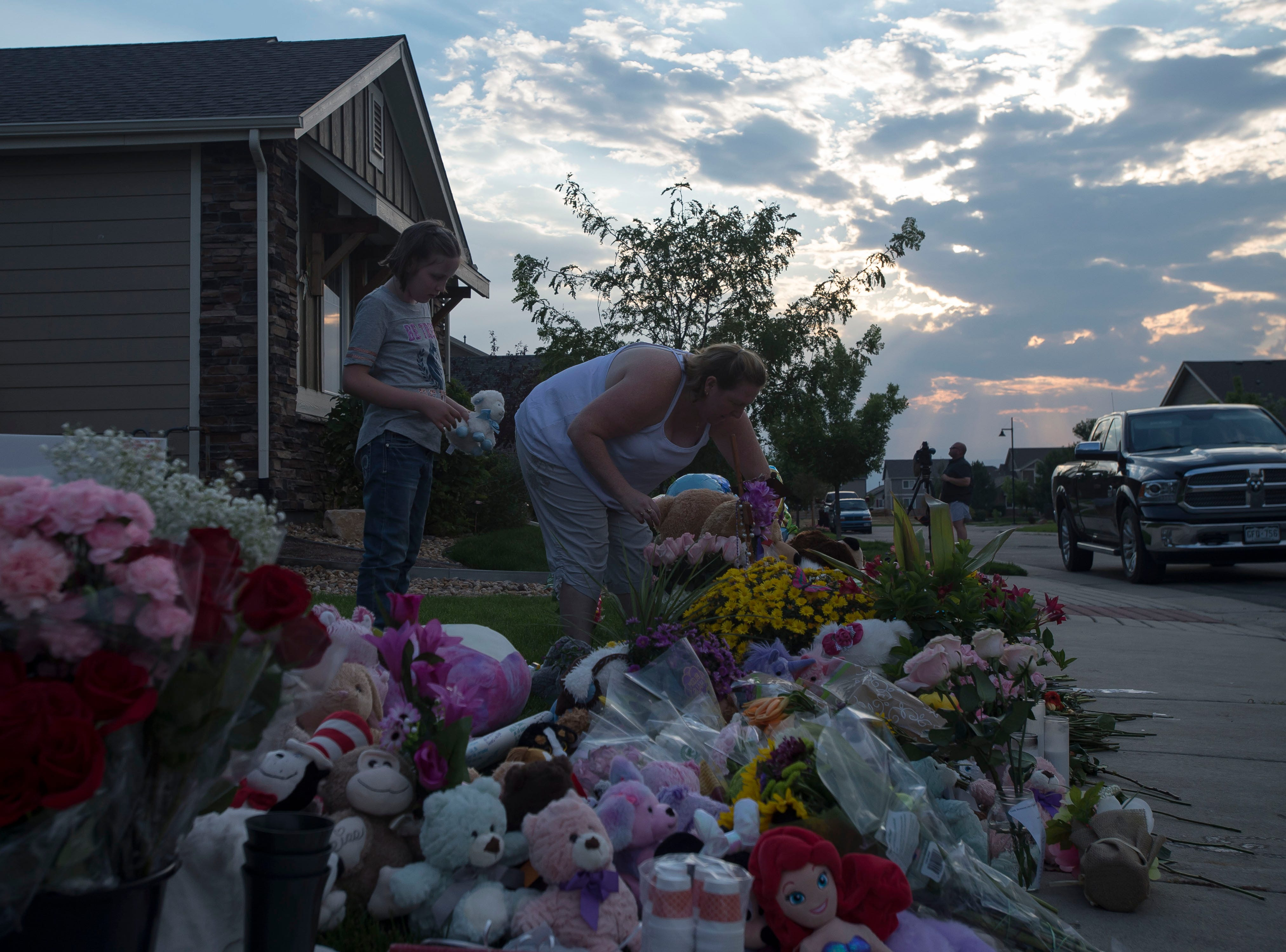 Kimberly and daughter Abigail Londen, 10, place flowers on a memorial before a candle-lit vigil for the slain Shanann Watts and her two daughters, Bella, 4, and Celeste, 3, in front of the Watts' family home on Friday, Aug. 17, 2018, in Frederick, Colo.