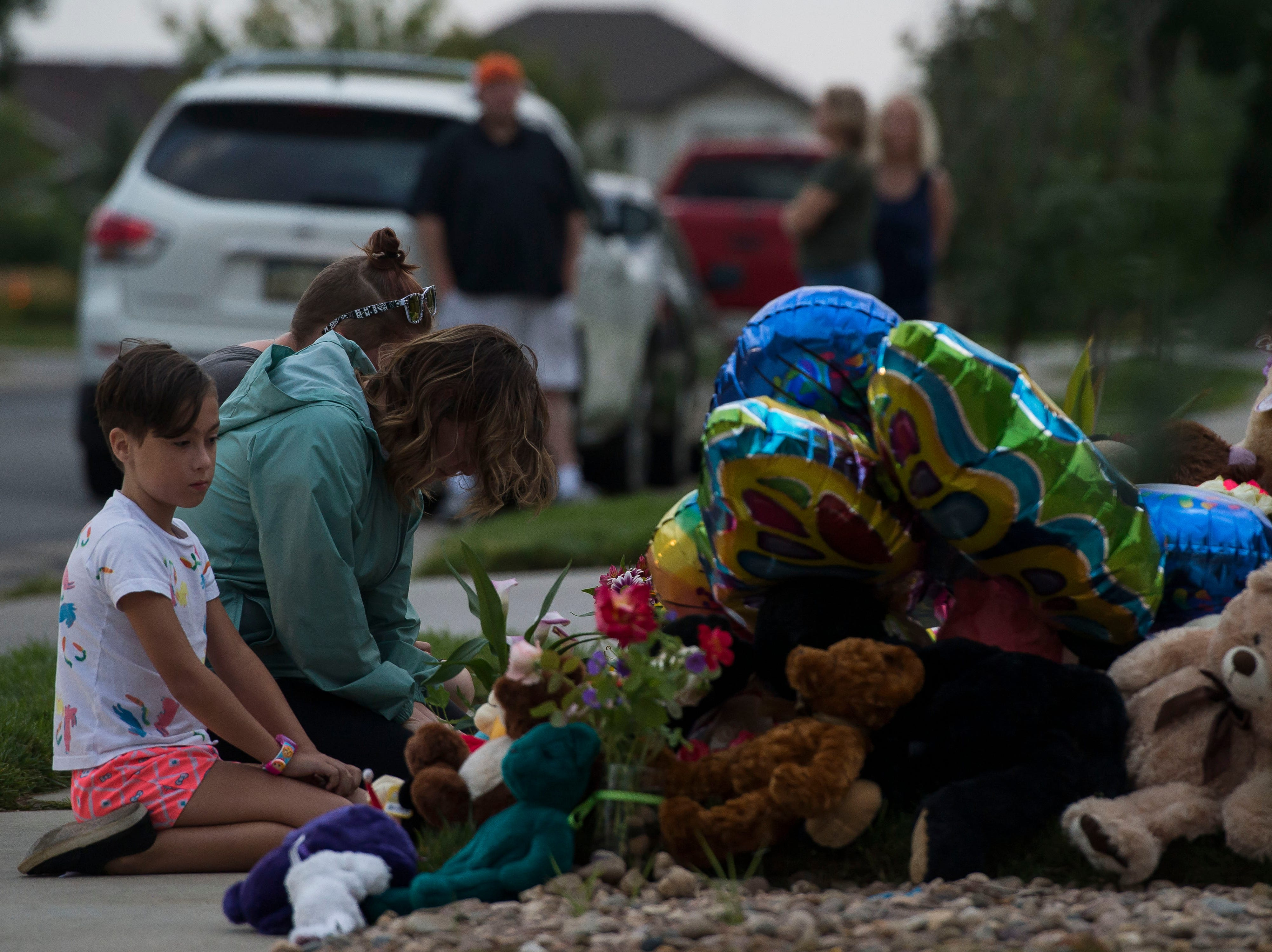 Brandi Banning lowers her head while visiting a memorial for the slain Shanann Watts and her two daughters, Bella, 4, and Celeste, 3, in front of the Watts' family home on Friday, Aug. 17, 2018, in Frederick, Colo.
