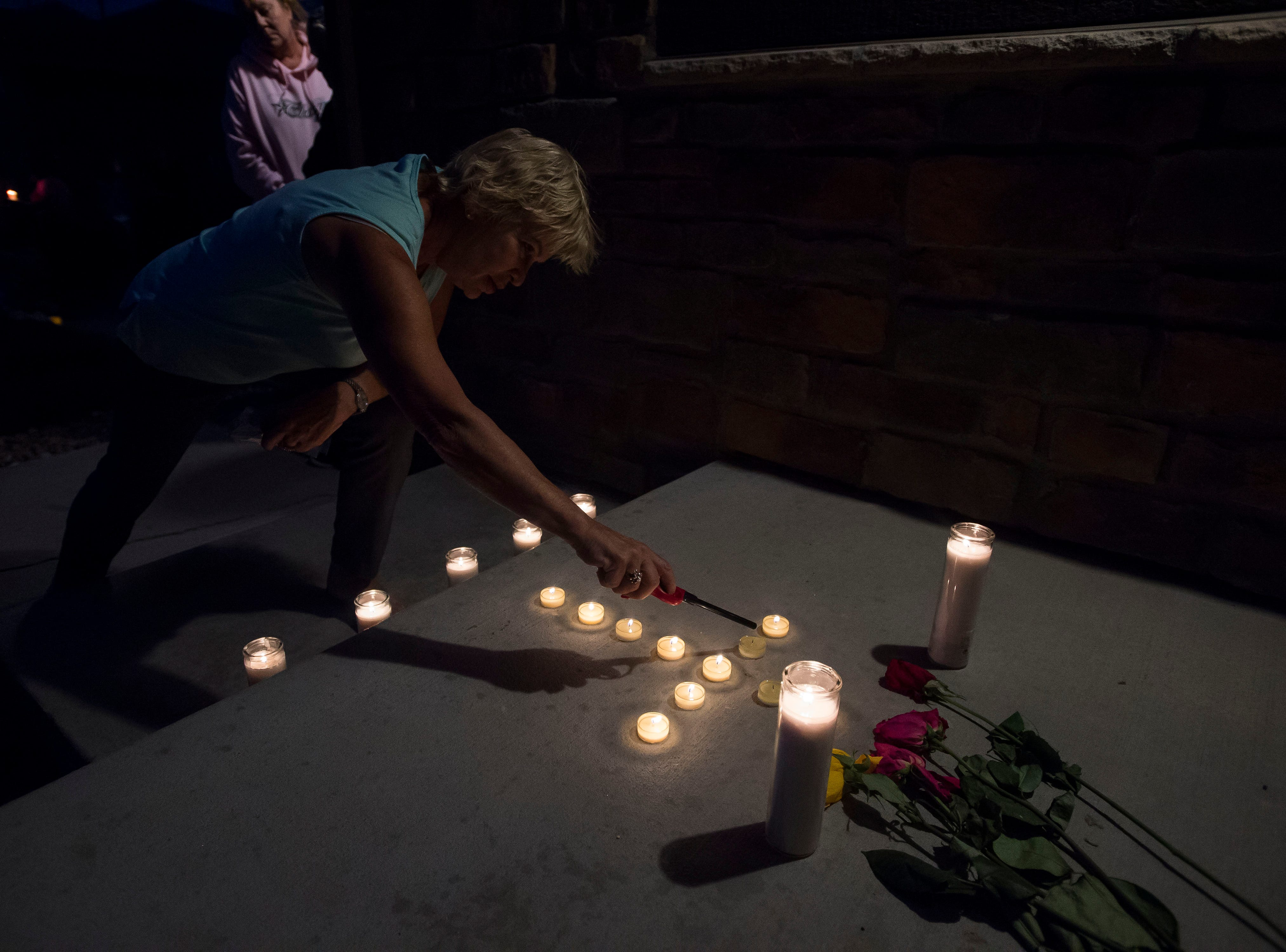 Neighborhood resident Mary Ann Bogner lights candles on the front porch during a candle-lit vigil for the slain Shanann Watts and her two daughters, Bella, 4, and Celeste, 3, in front of the Watts' family home on Friday, Aug. 17, 2018, in Frederick, Colo.
