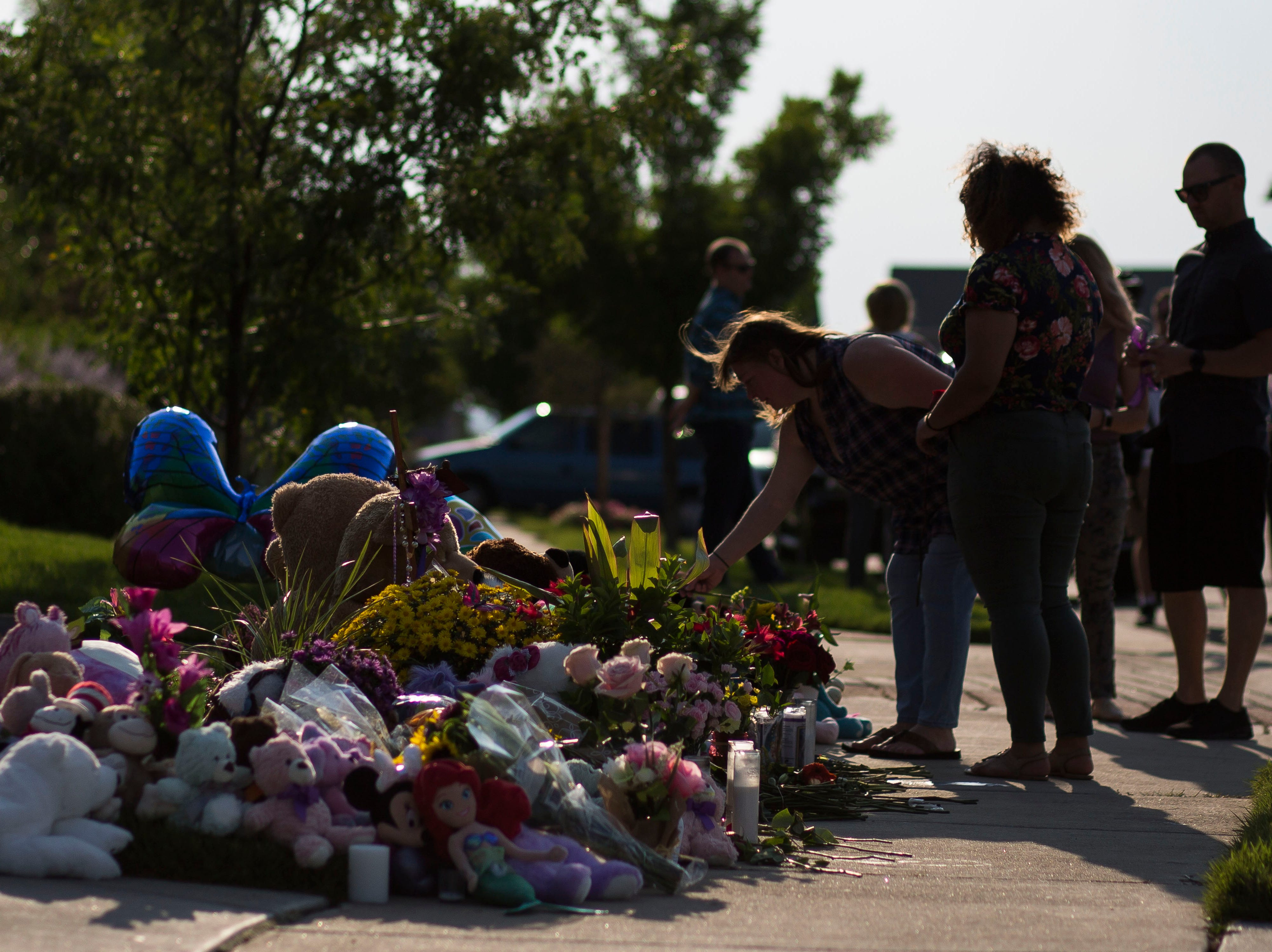 Frederick resident Jeniffer Seiler places a flower on the memorial for the slain Shanann Watts and her two daughters, Bella, 4, and Celeste, 3, in front of the Watts' family home on Friday, Aug. 17, 2018, in Frederick, Colo.