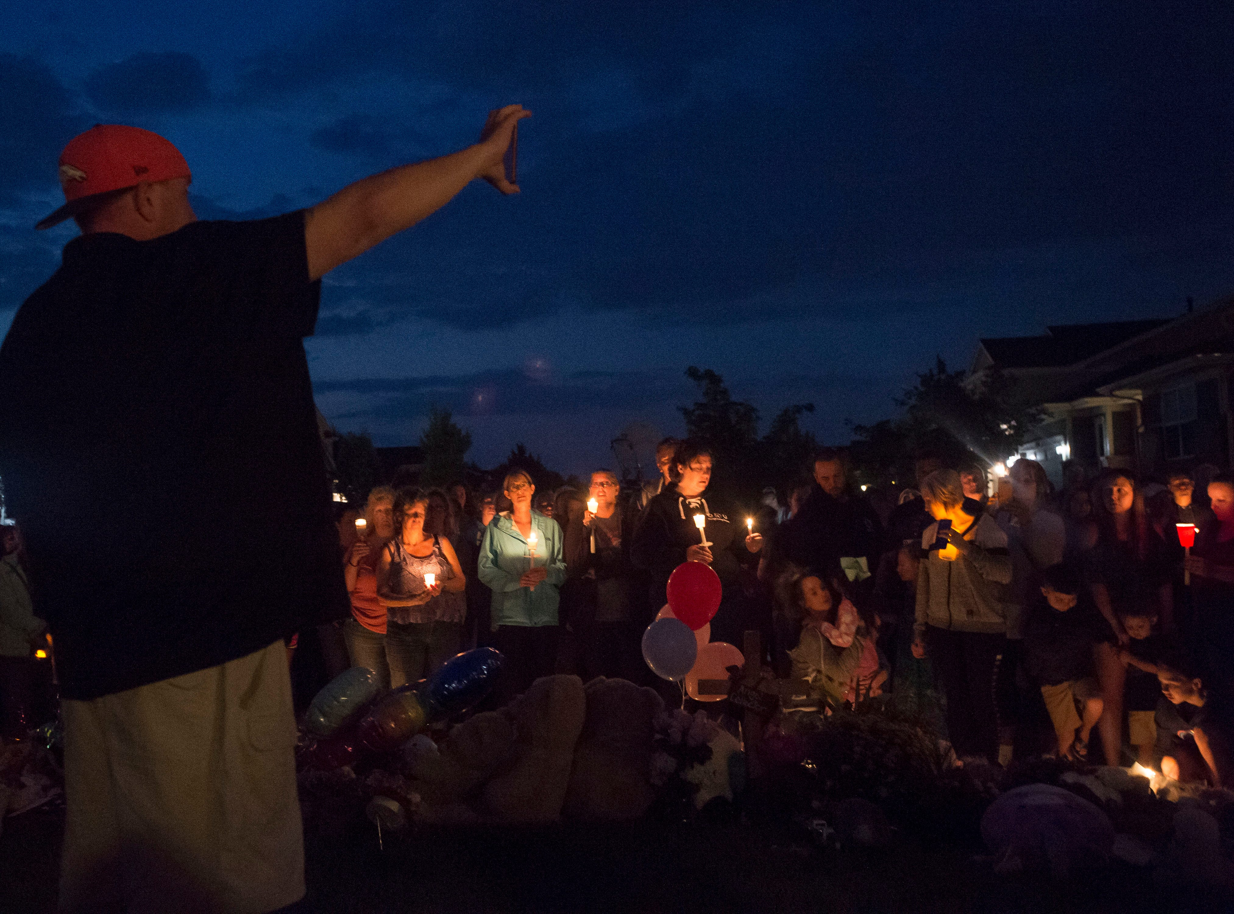 A neighbor holds a phone up to the crowd while live-streaming to Shannon Watts' parents to let them see the local outpouring of support during a candle-lit vigil for the slain Shanann Watts and her two daughters, Bella, 4, and Celeste, 3, in front of the Watts' family home on Friday, Aug. 17, 2018, in Frederick, Colo.