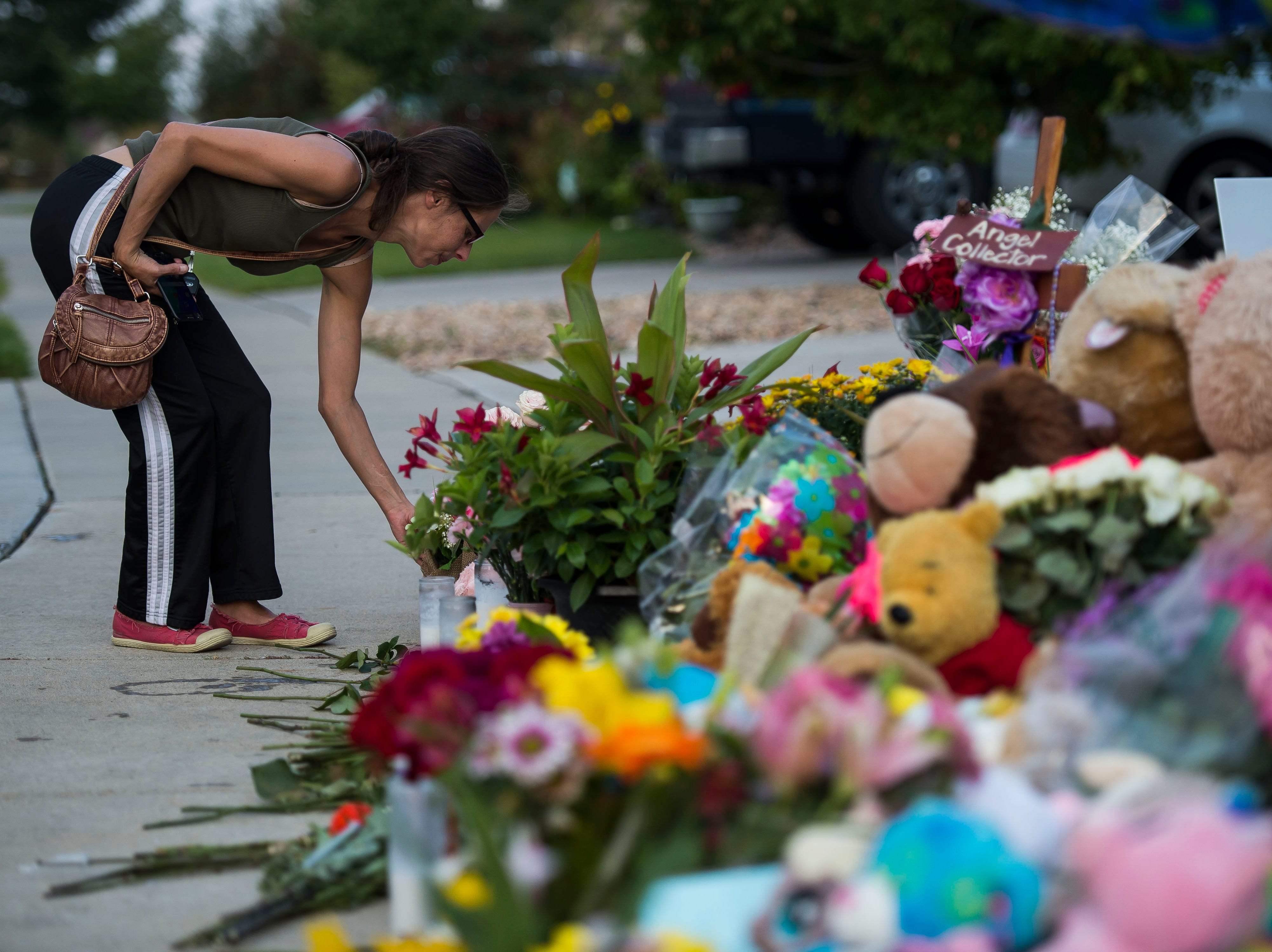 Aurora resident Kristina Hapner straitens flowers and stuffed animals at a memorial for the slain Shanann Watts and her two daughters, Bella, 4, and Celeste, 3, in front of the Watts' family home on Friday, Aug. 17, 2018, in Frederick, Colo.