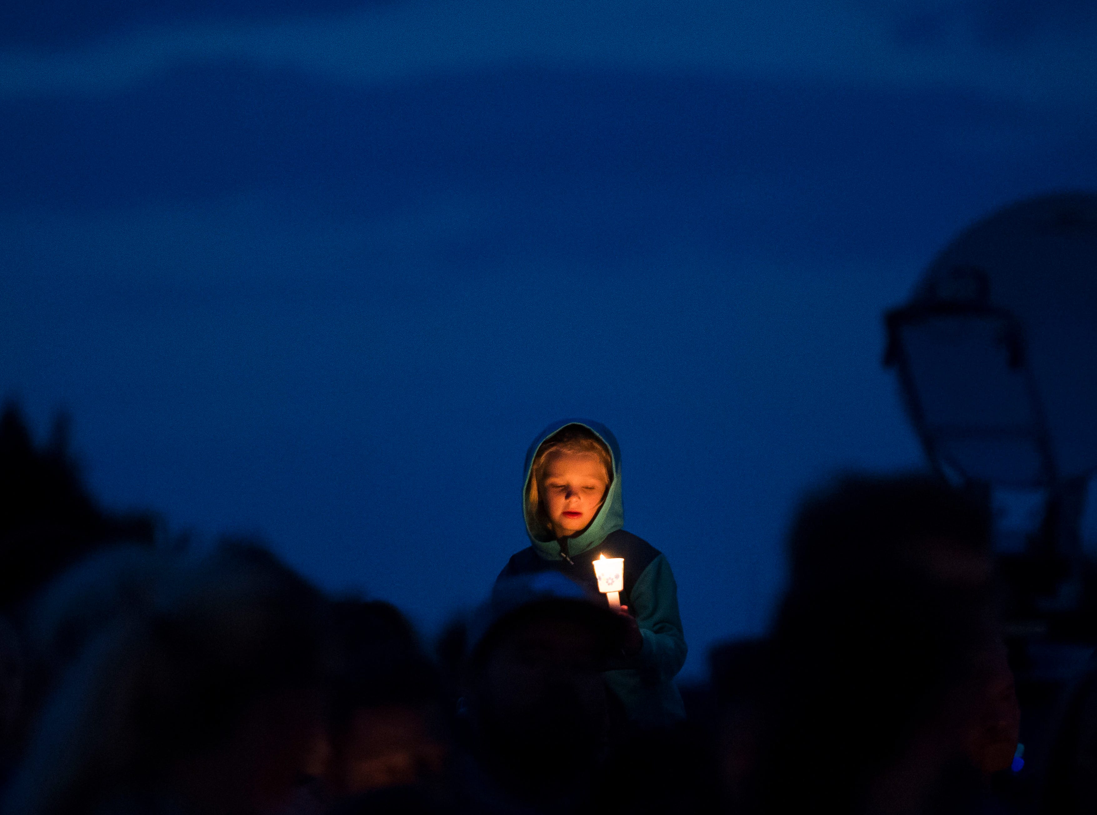 A child holds a candle while sitting on an adult's shoulders at a candle-lit vigil for the slain Shanann Watts and her two daughters, Bella, 4, and Celeste, 3, in front of the Watts' family home on Friday, Aug. 17, 2018, in Frederick, Colo.