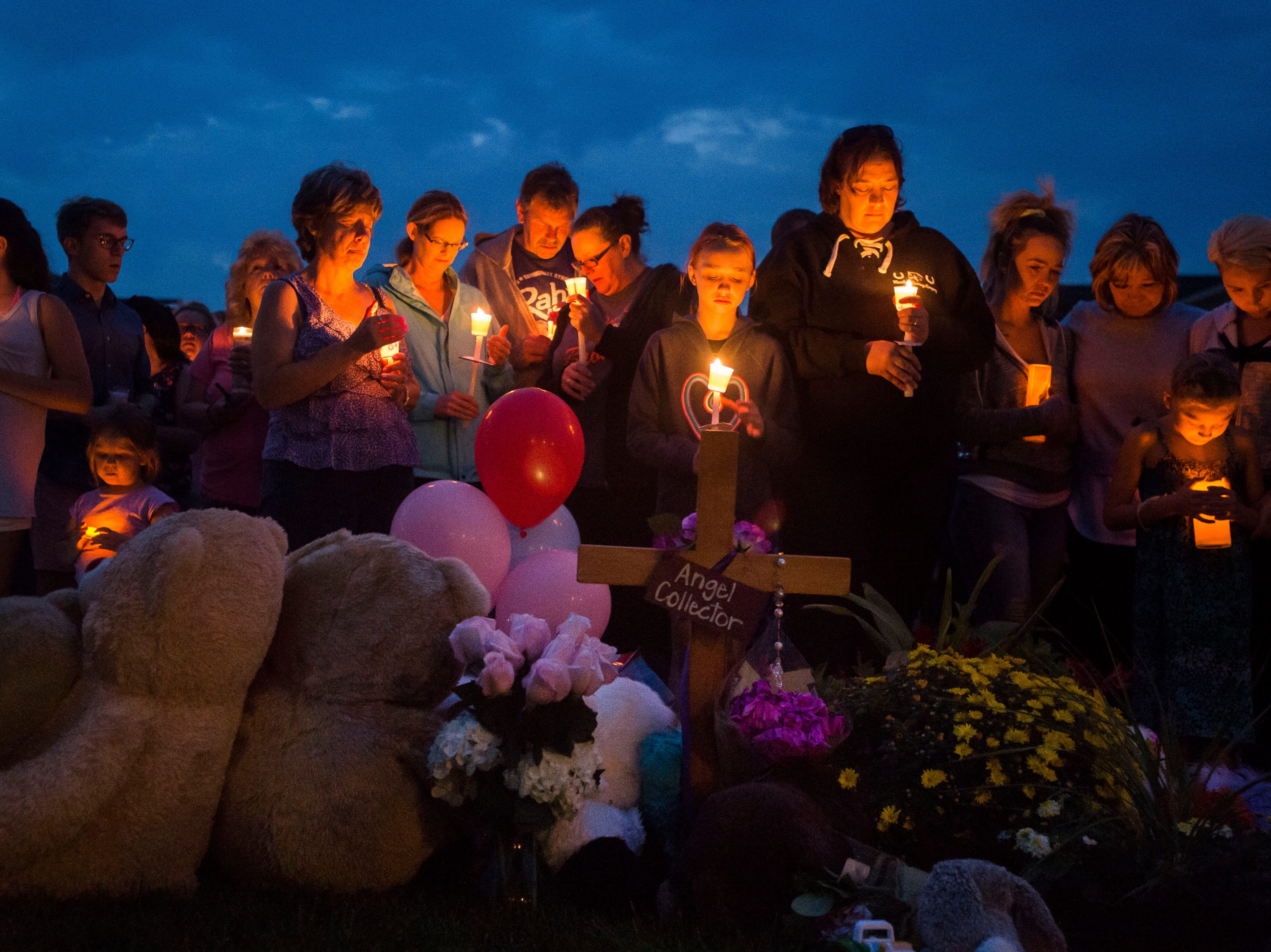 Mourners gather in front of a memorial for a candle-lit vigil for the slain Shanann Watts and her two daughters, Bella, 4, and Celeste, 3, in front of the Watts' family home on Friday, Aug. 17, 2018, in Frederick, Colo.