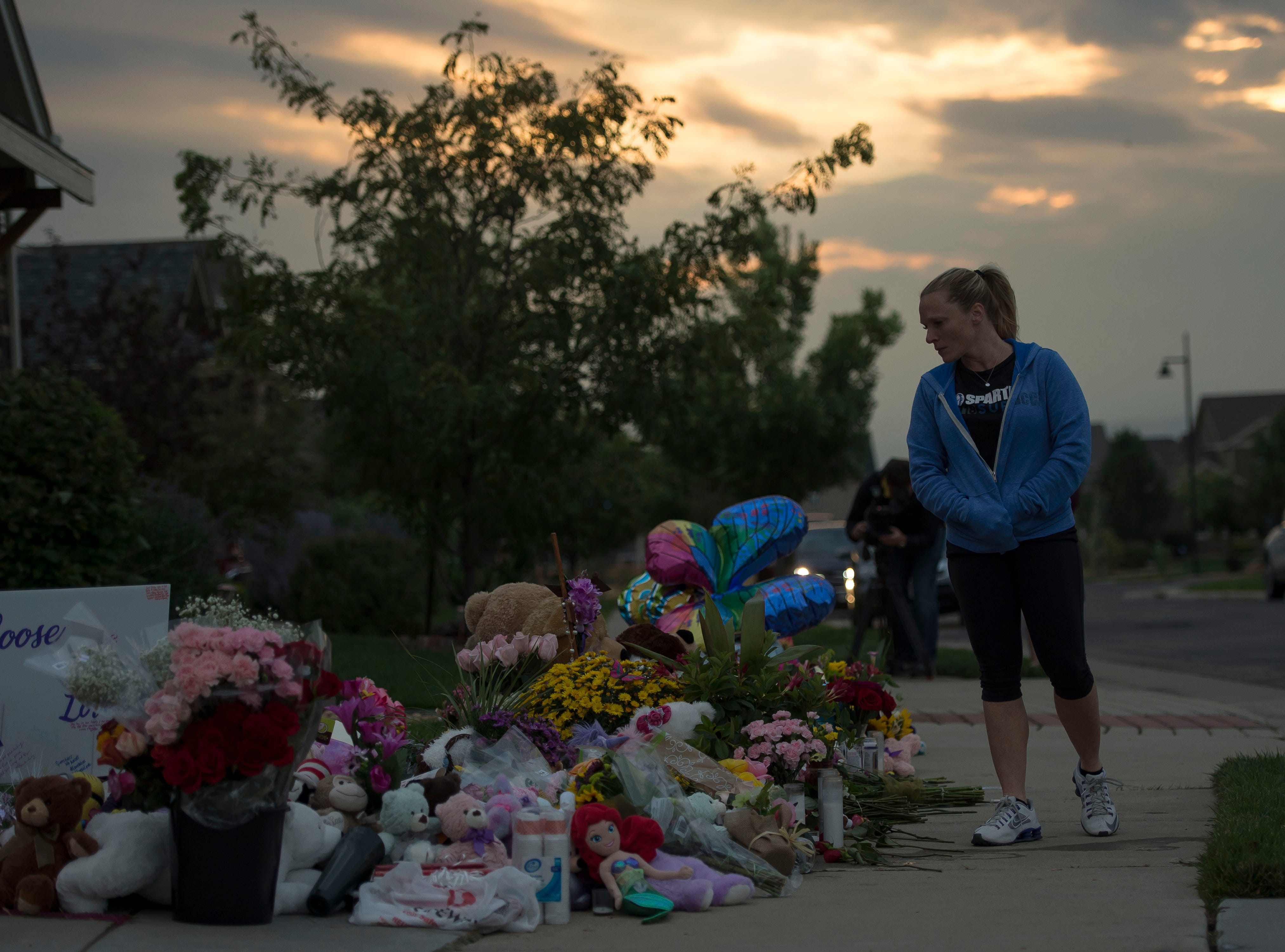 Firestone resident Reesa Rennecker walks by a memorial before a candle-lit vigil for the slain Shanann Watts and her two daughters, Bella, 4, and Celeste, 3, in front of the Watts' family home on Friday, Aug. 17, 2018, in Frederick, Colo.