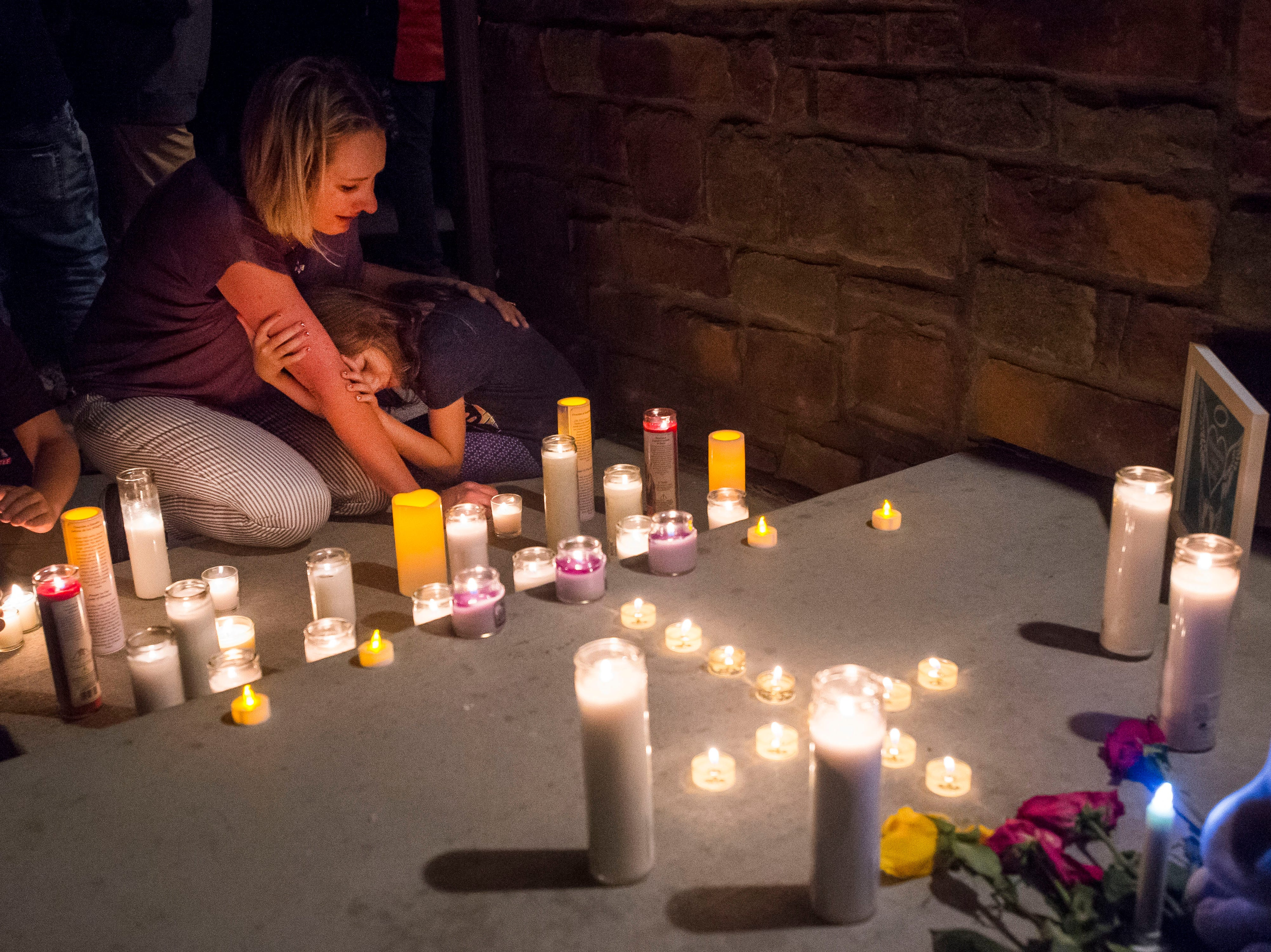 Jeanna Dietz hugs her daughter Eva, 7, while looking onto memorial on the front porch while others gather for a candle-lit vigil for the slain Shanann Watts and her two daughters, Bella, 4, and Celeste, 3, in front of the Watts' family home on Friday, Aug. 17, 2018, in Frederick, Colo.