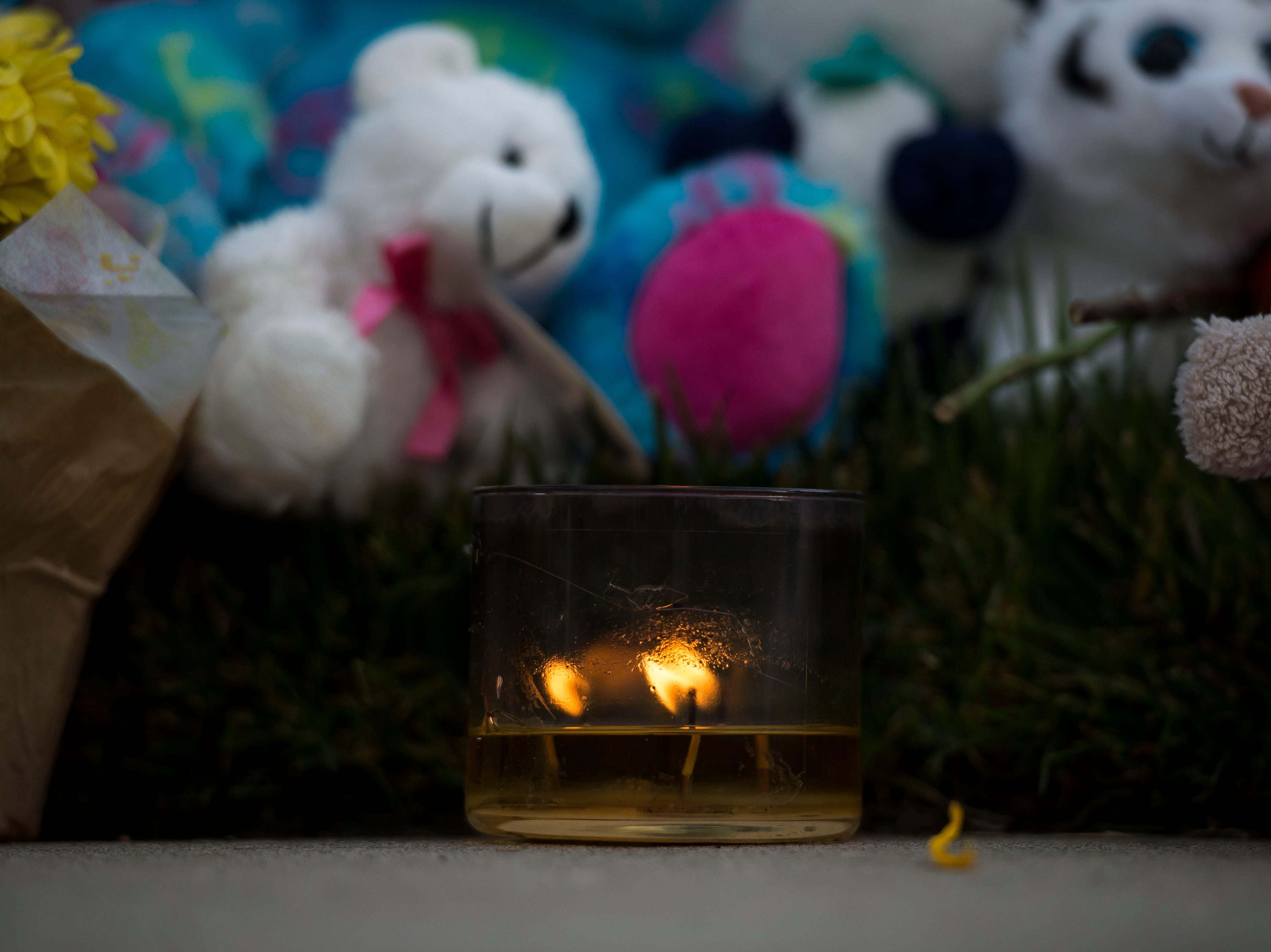 A single candle burns in front of a memorial for the slain Shanann Watts and her two daughters, Bella, 4, and Celeste, 3, in front of the Watts' family home on Friday, Aug. 17, 2018, in Frederick, Colo.