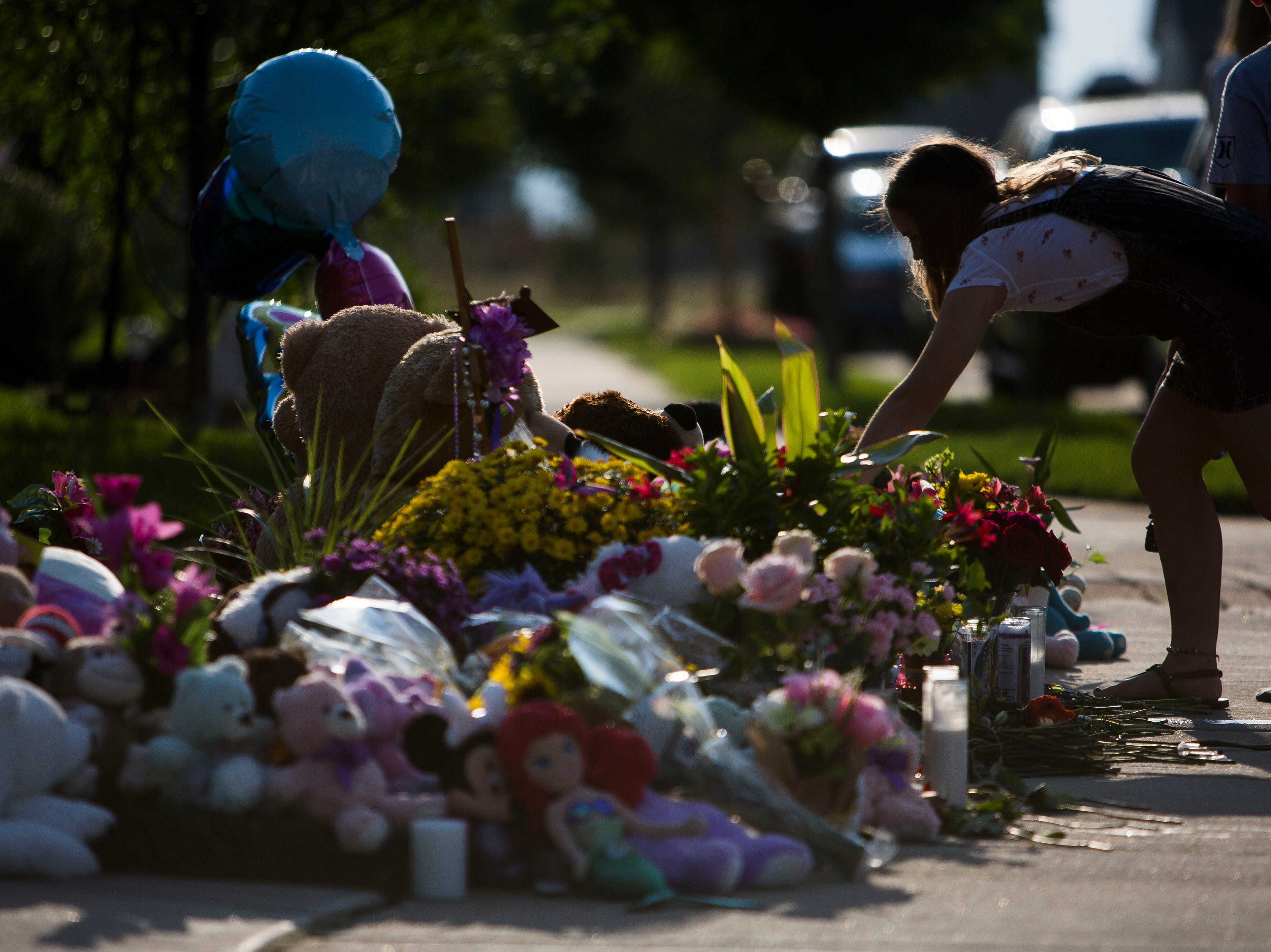 Frederick resident Elaina Dwinal, 16, leans over a memorial of flowers, stuffed animals and hand-written notes for the slain Shanann Watts and her two daughters, Bella, 4, and Celeste, 3, in front of the Watts' family home on Friday, Aug. 17, 2018, in Frederick, Colo.