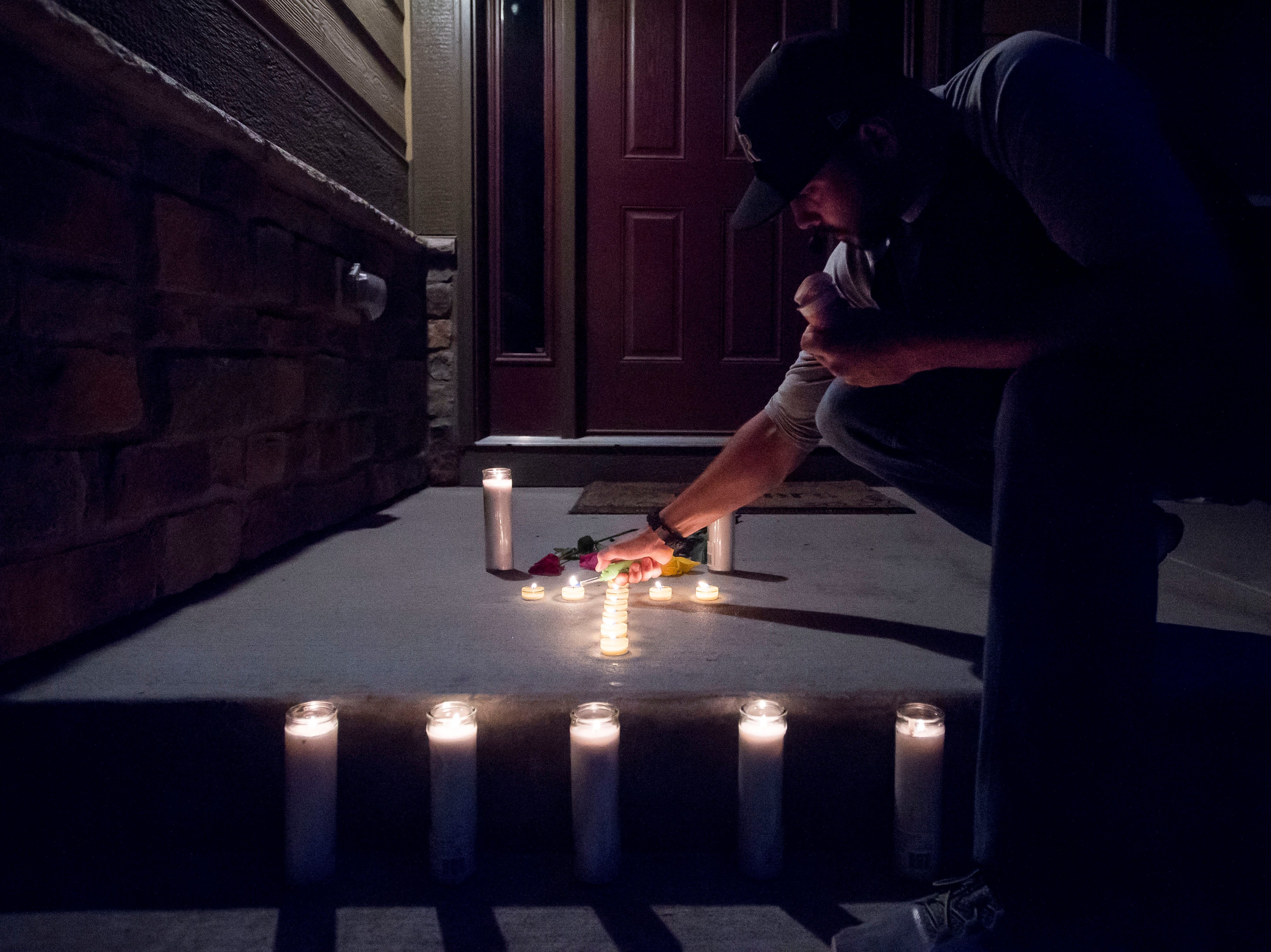 Tyler Sister, from Longmont, helps relight a candle in a memorial placed on the front porch while others gather for a candle-lit vigil for the slain Shanann Watts and her two daughters, Bella, 4, and Celeste, 3, in front of the Watts' family home on Friday, Aug. 17, 2018, in Frederick, Colo.